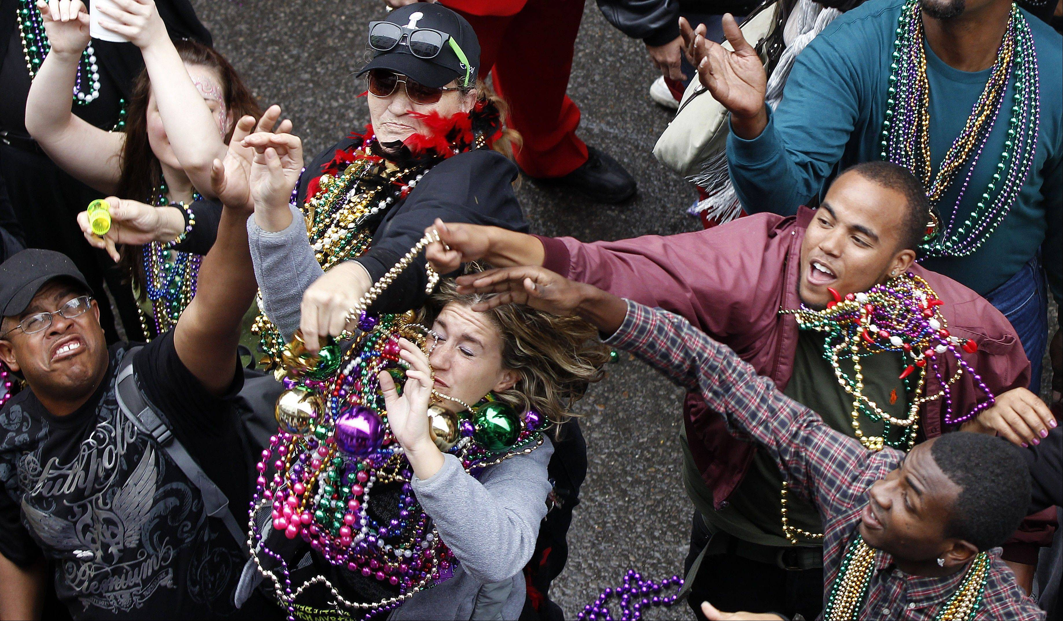 Revelers grab for beads as they are tossed from the balcony of the Royal Sonesta Hotel on Bourbon Street during Mardi Gras in New Orleans, Tuesday, Feb. 12, 2013.