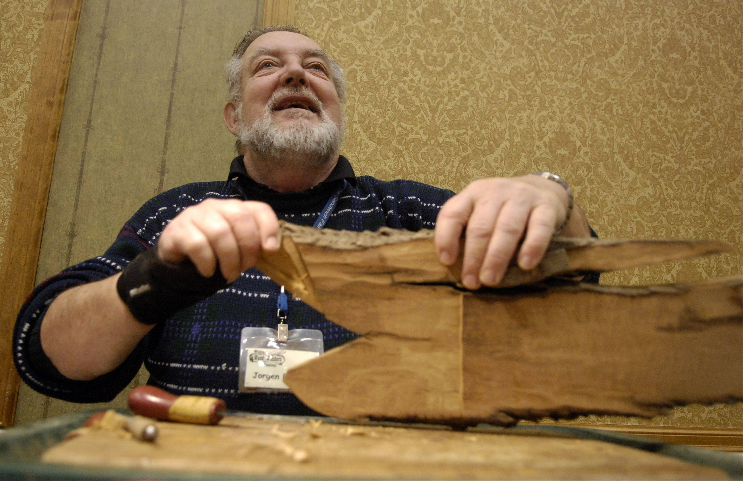 Jorgen Poulsen of Sandwich takes a break from working on a cottonwood bark carving to talk with a visitor at his display at a previous Winter Wood Wonders Festival.