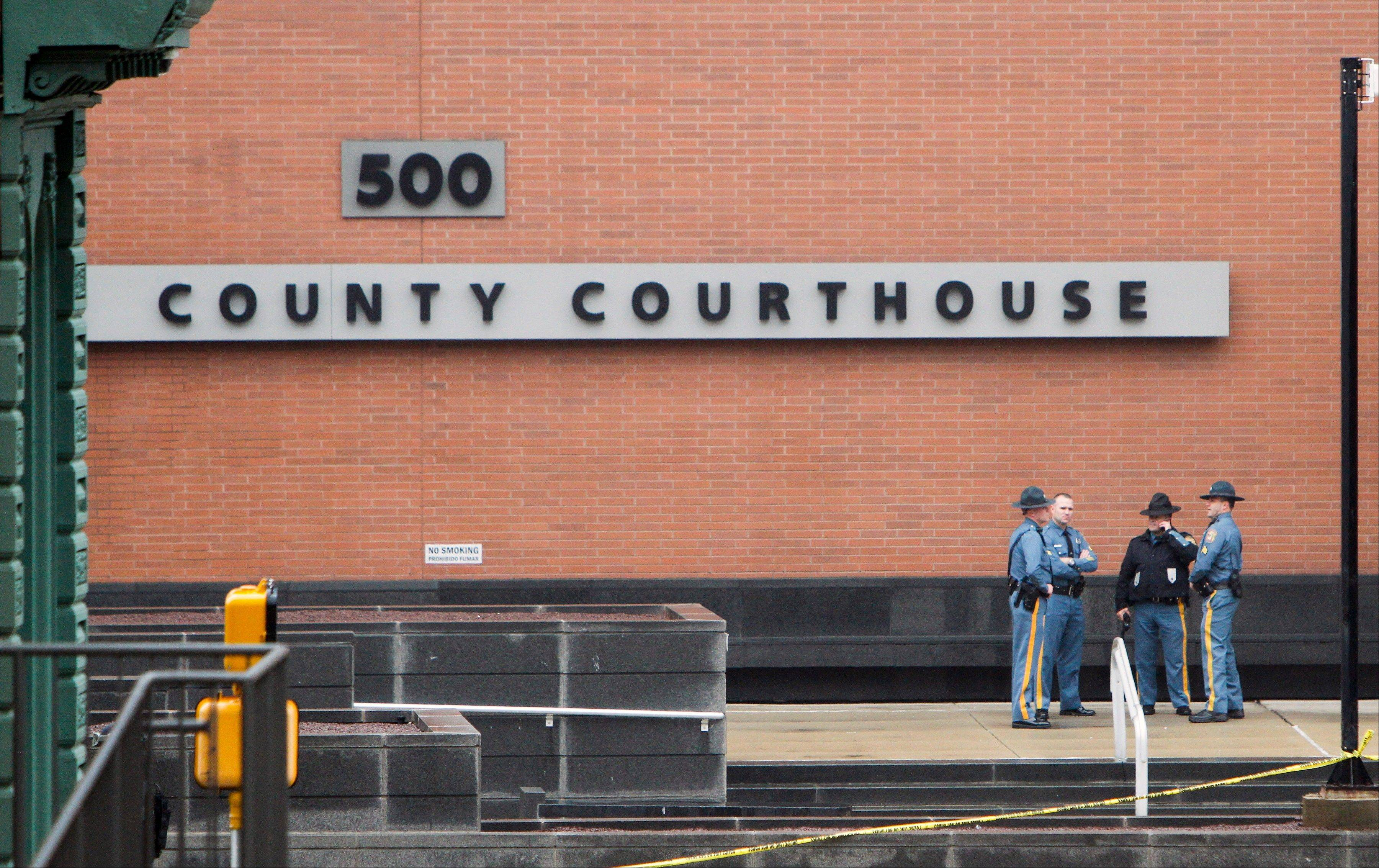 Law enforcement officials and investigators gather outside the New Castle County Courthouse in Wilmington, Del. on Monday, Feb. 11, 2013, after three people died Monday morning in a shooting at a courthouse, including the shooter, authorities said.