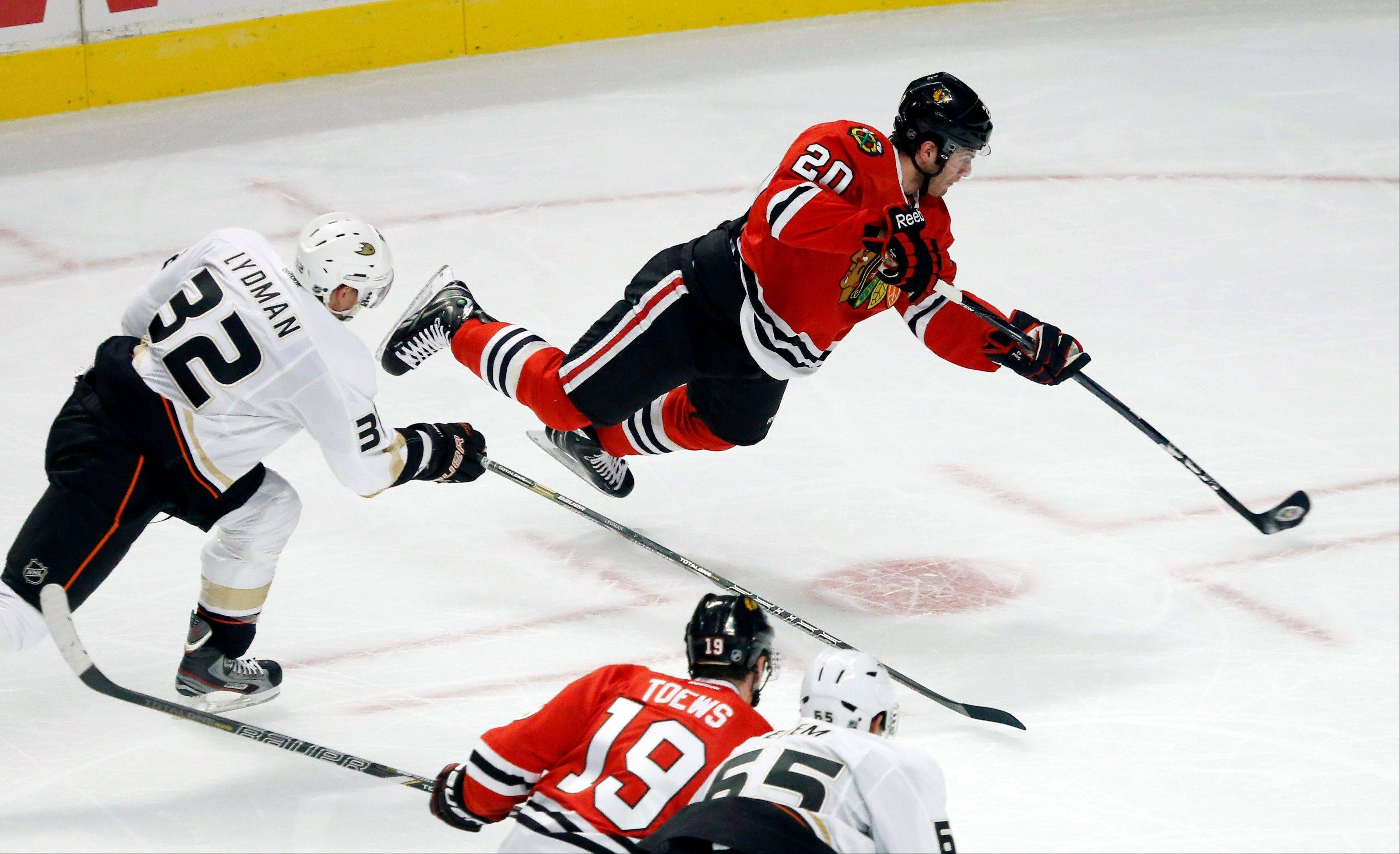 The Blackhawks' Brandon Saad goes airborne and shoots past Ducks defenseman Toni Lydman as the Hawks' Jonathan Toews and the Ducks' Emerson Etem watch during the second period Tuesday night. After a review, Saad was credited with the goal to give the Hawks a 2-1 lead.