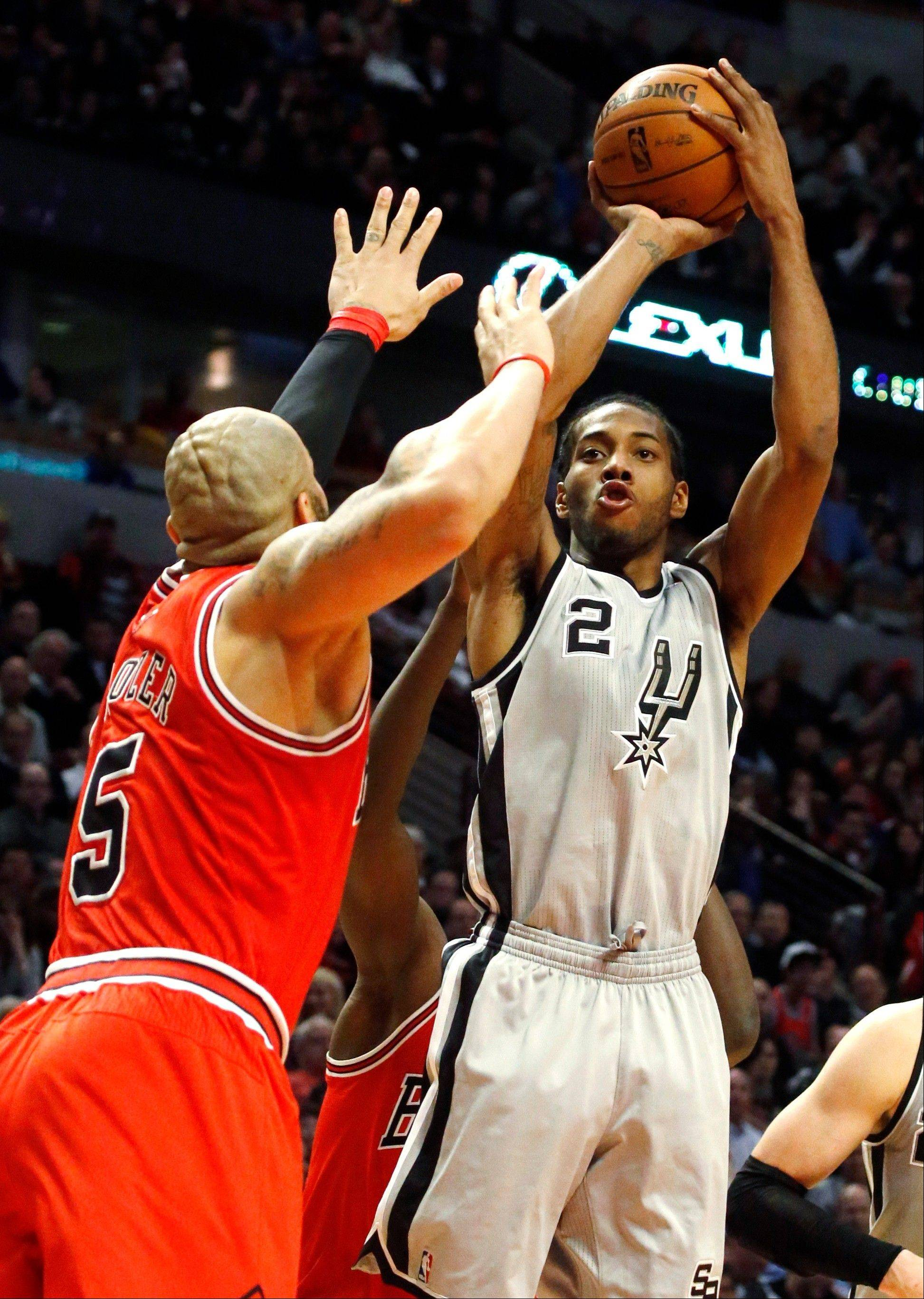 Spurs forward Kawhi Leonard shoots over Bulls forward Carlos Boozer during the second half Monday night at the United Center.