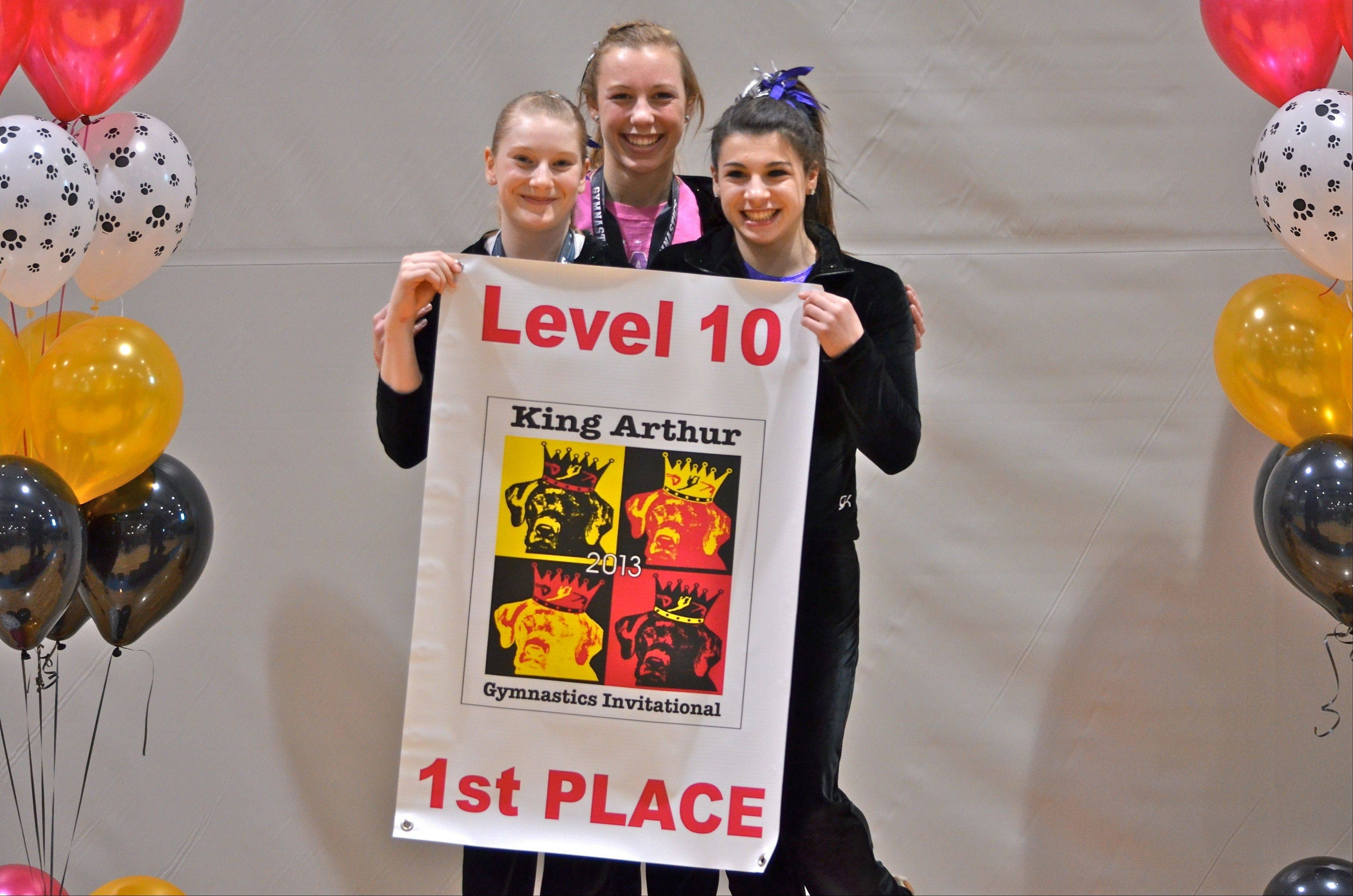 Proudly displaying their first-place banner from the recent King Arthur meet are the Level 10 girls from Ultimate Gymnastics of Gurnee. Competing at the Bourbonnais meet were, from left, Lauren Marshall, Emily Basara and Ally Hoyer.