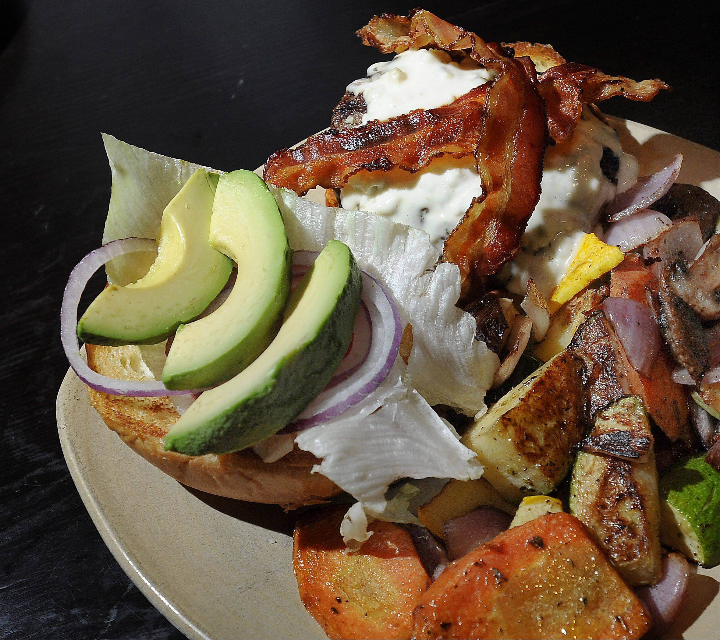 McMae's black and blue burger features blue cheese and bacon. It comes topped with avocado, lettuce and tomato.