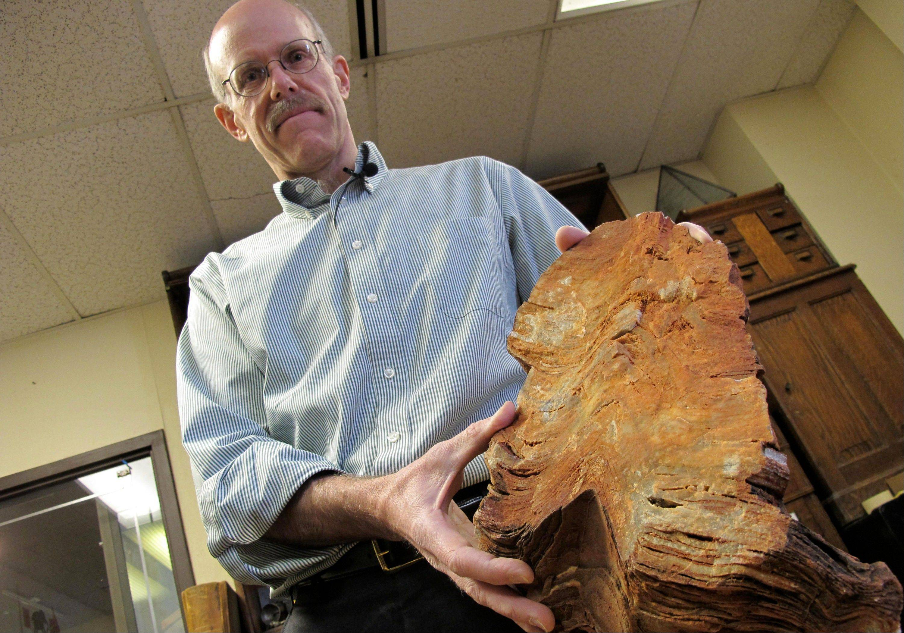 University of Wisconsin-Madison Geoscientist Clark Johnson holds what he says is a 3.5 billion year old rock in Madison, Wis. Johnson is leading a team of scientists and others studying Earth rocks that are billions of years old looking for crucial information to understand how life might have arisen elsewhere in the universe and guide the search for life on Mars one day.