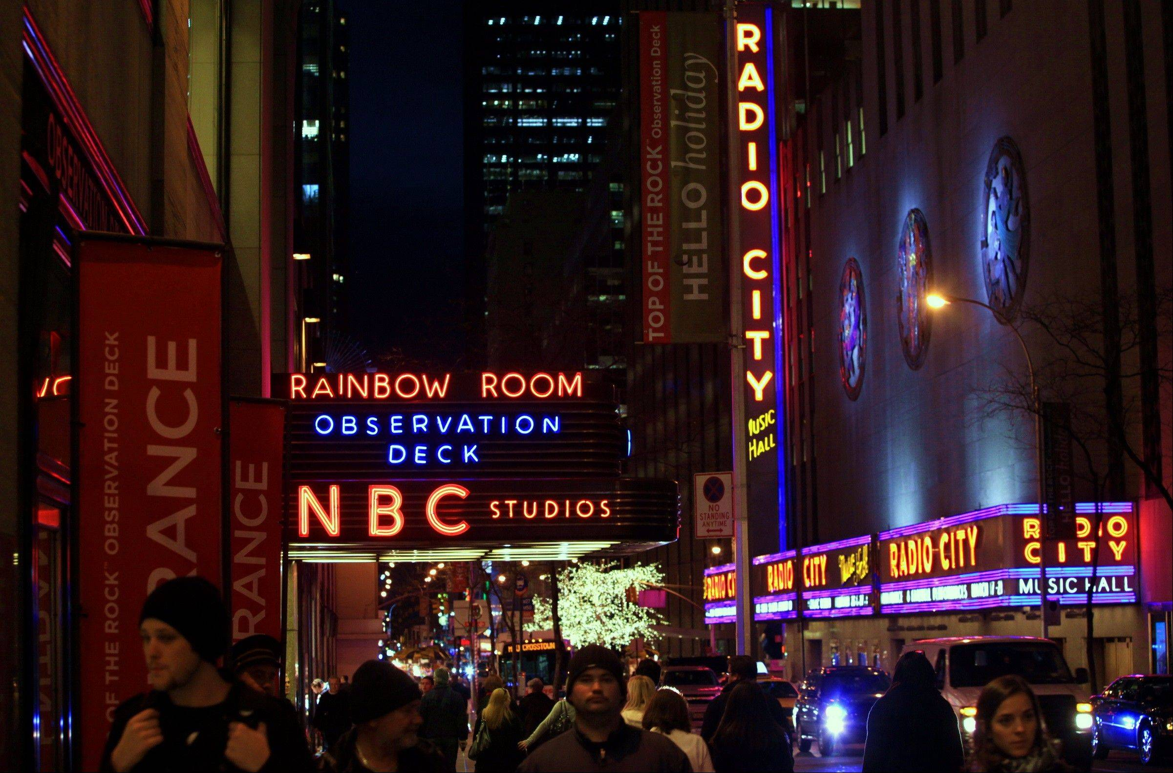 The NBC logo glows in neon lights among other iconic signs at its headquarters in New York. Comcast said Tuesday that it's buying General Electric's 49 percent stake in the NBCUniversal joint venture for $16.7 billion.