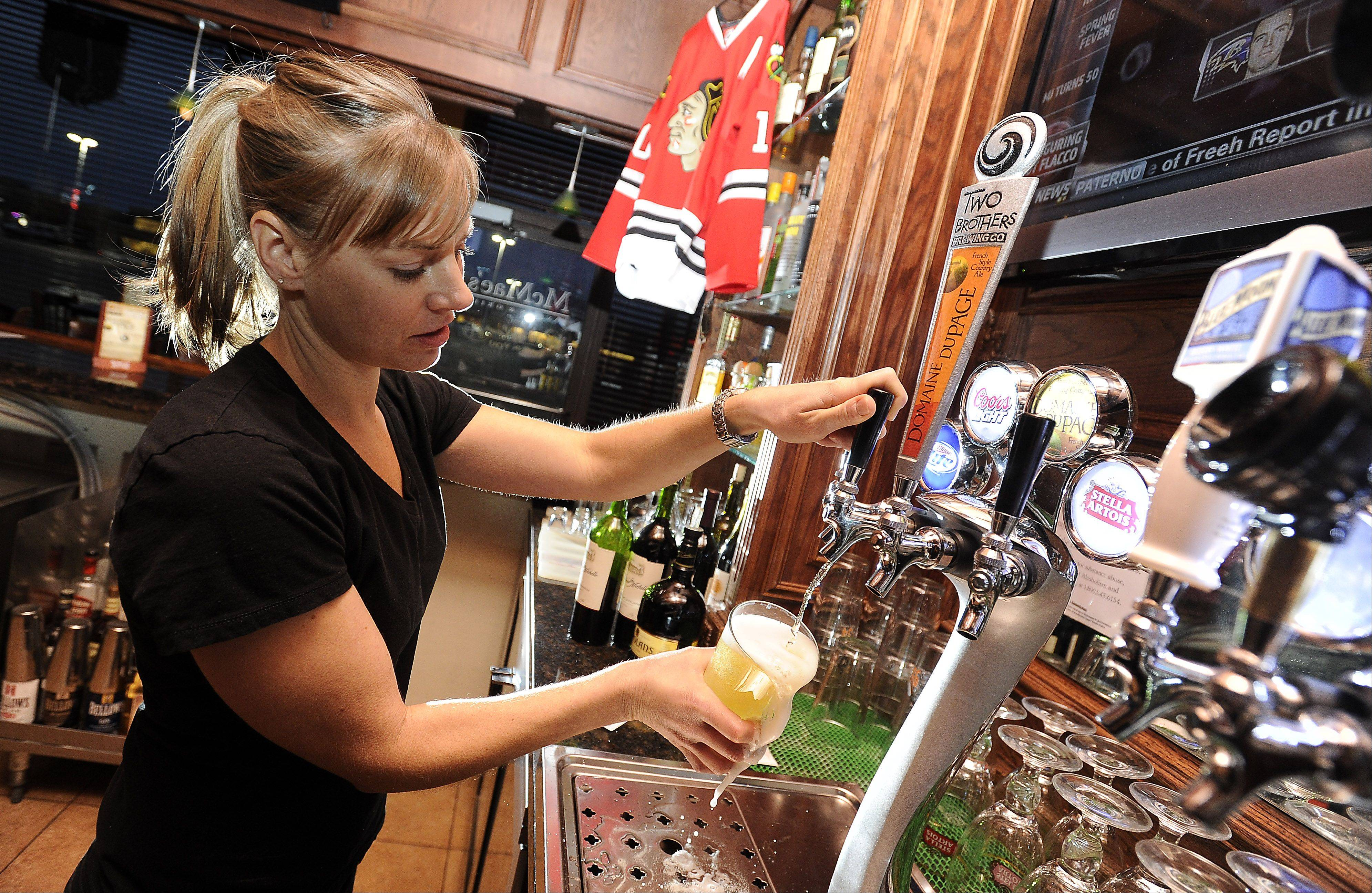 Bartender Cindy Stutz of South Elgin taps a beer at McMae's Tavern & Grill in Bartlett.