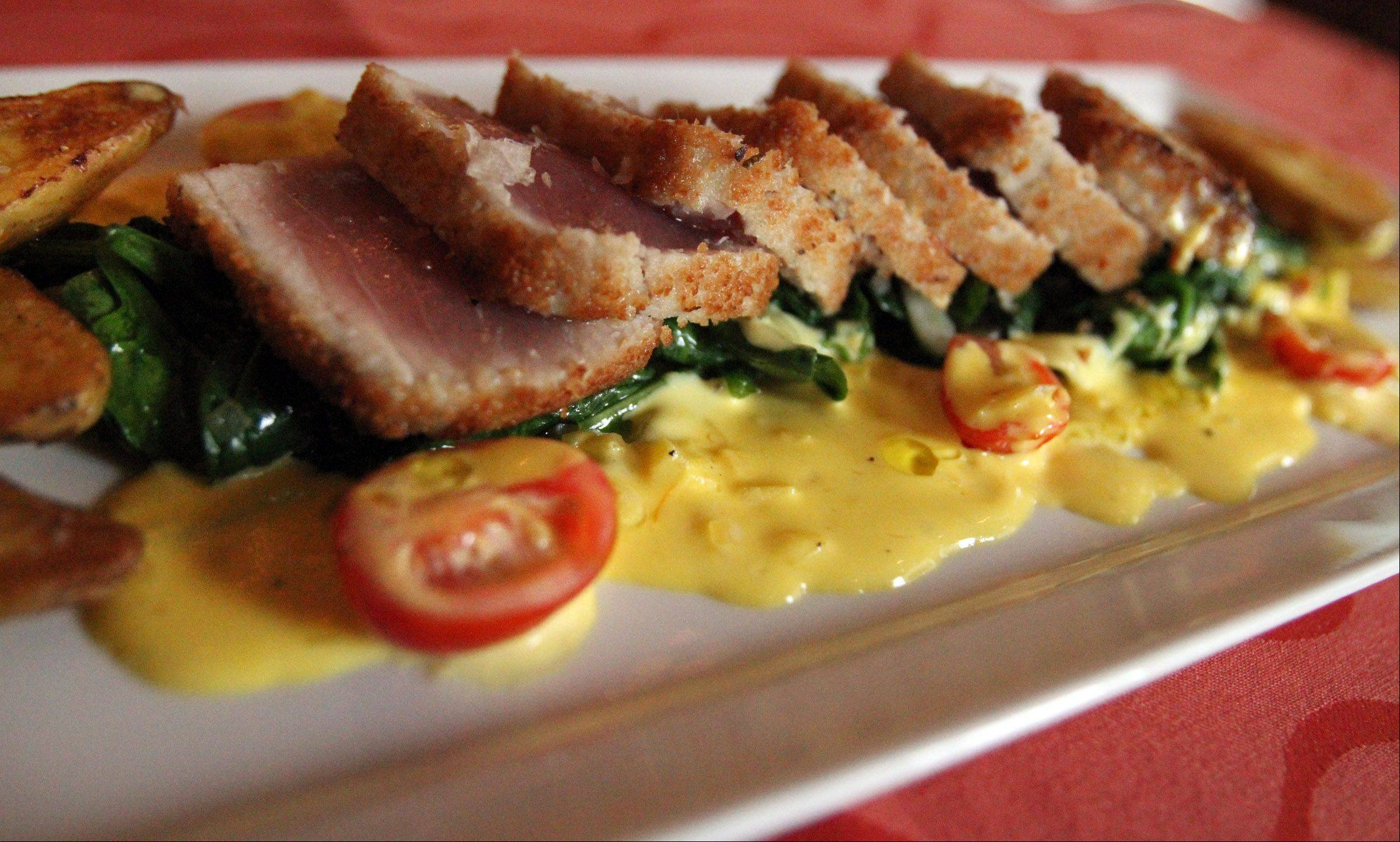 Spanish-inspired citrus-crusted ahi tuna comes with spinach, fennel, saffron cream, fingerling potatoes and grape tomatoes.