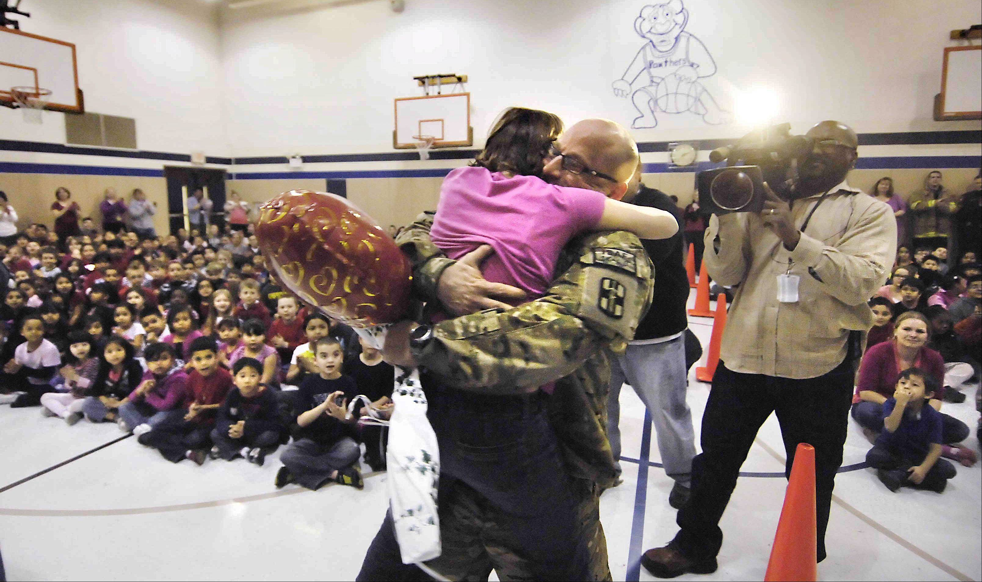 Lt. Jordon Wolf hugs his daughter Kayla, a fifth-grader at Ridge Circle Elementary School in Streamwood, after he surprised her during an assembly Thursday. He had been deployed in Afghanistan since April.