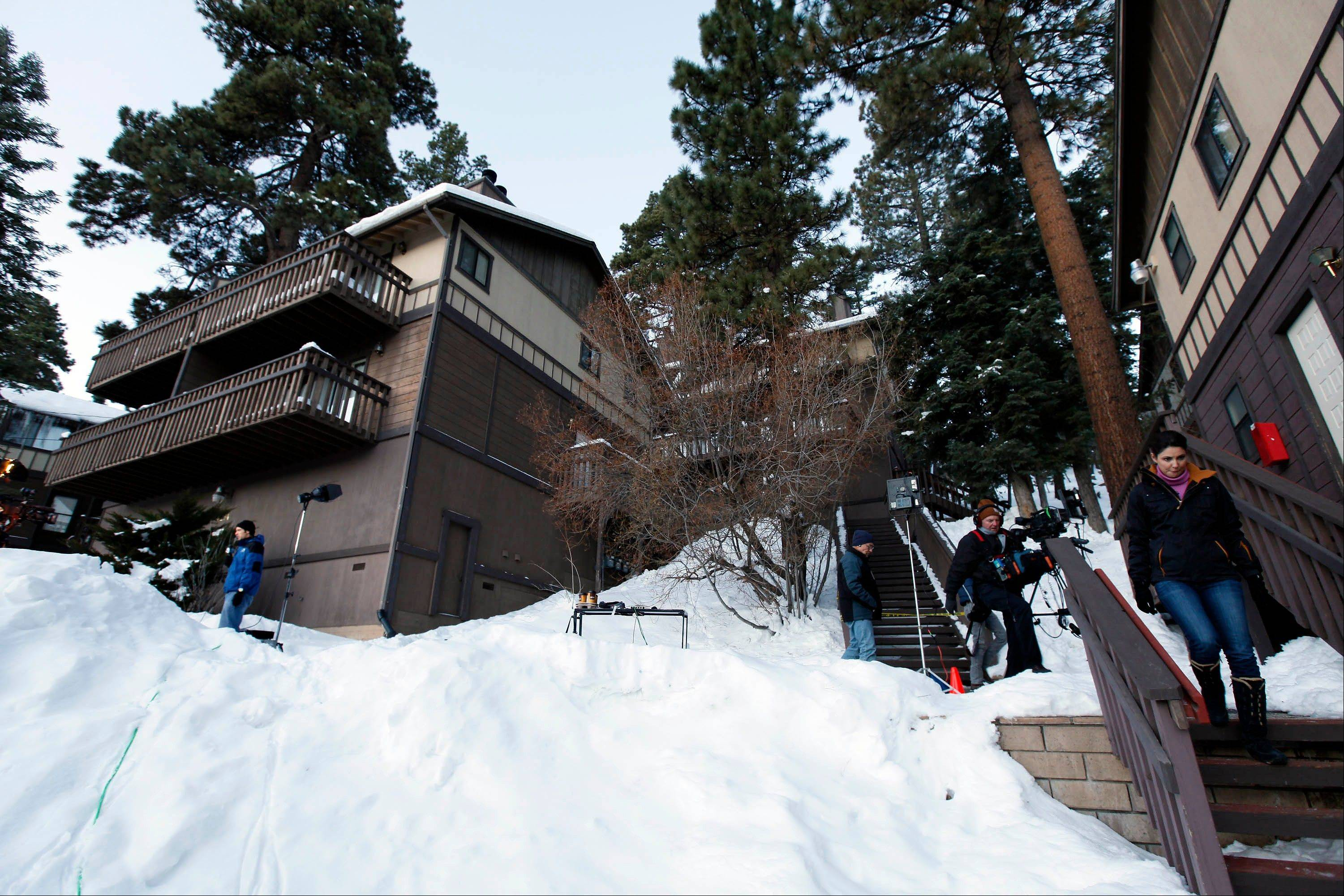 Members of the news media are shown outside a home, at left, in Big Bear, Calif., where two women were taken hostage by fugitive Christopher Dorner. Police scoured mountain peaks for days but had no idea he was hiding among them, possibly holed up in this vacation home across the street from their command post.