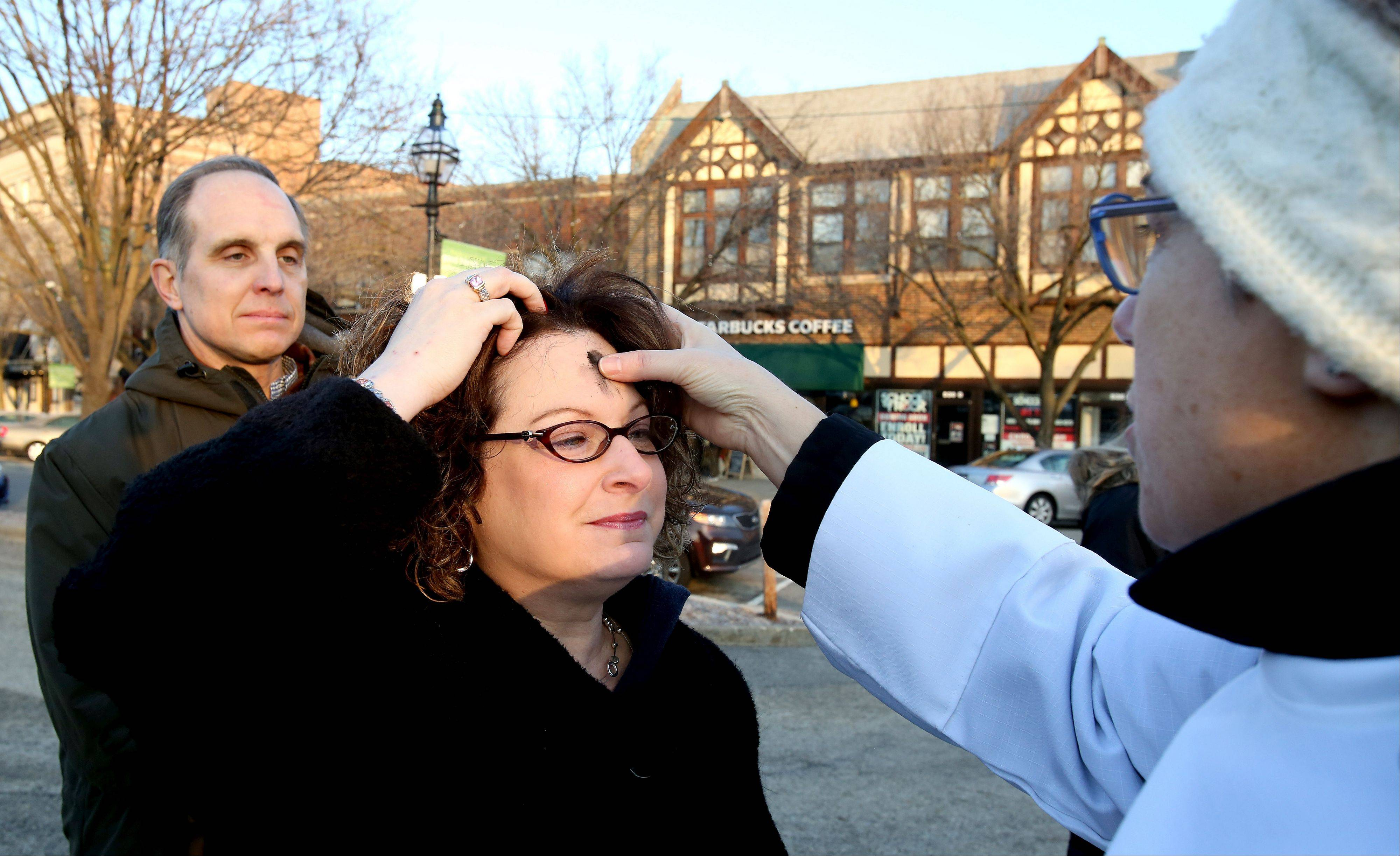 Kristin Progar of Glen Ellyn receives ashes from Charisse Jensen, a seminary intern with Faith Evangelical Lutheran Church, during Ashes to Go at the Glen Ellyn train station on Wednesday. Michael Progar, left, awaits his turn.