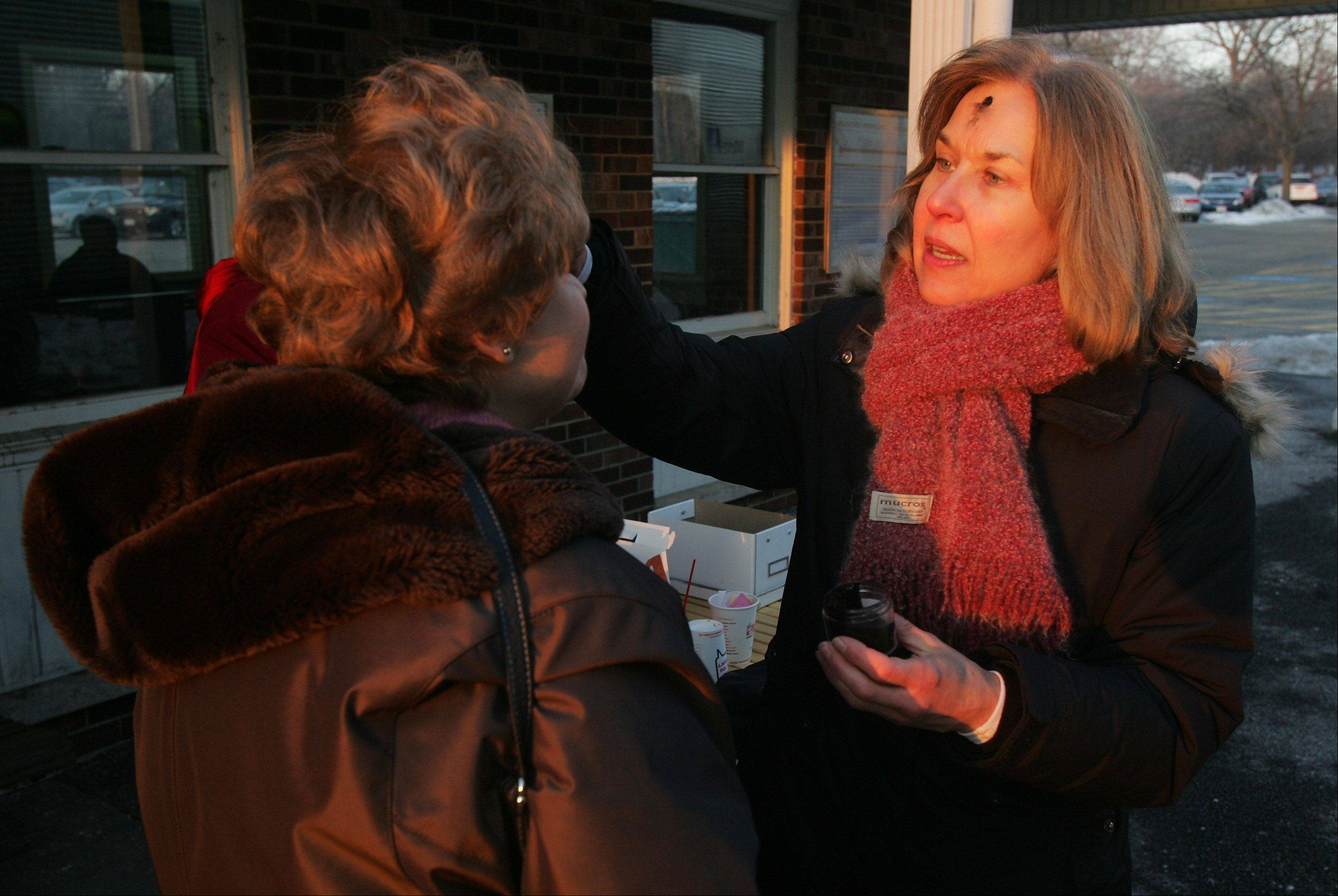 "The Rev. Patti Snickenberger, from St. Lawrence Episcopal Church in Libertyville, places ashes on the forehead of commuter Pat Vavrina, of Ingleside, on Ash Wednesday at the Libertyville Metra Station as part of the ""Ashes To Go"" program."