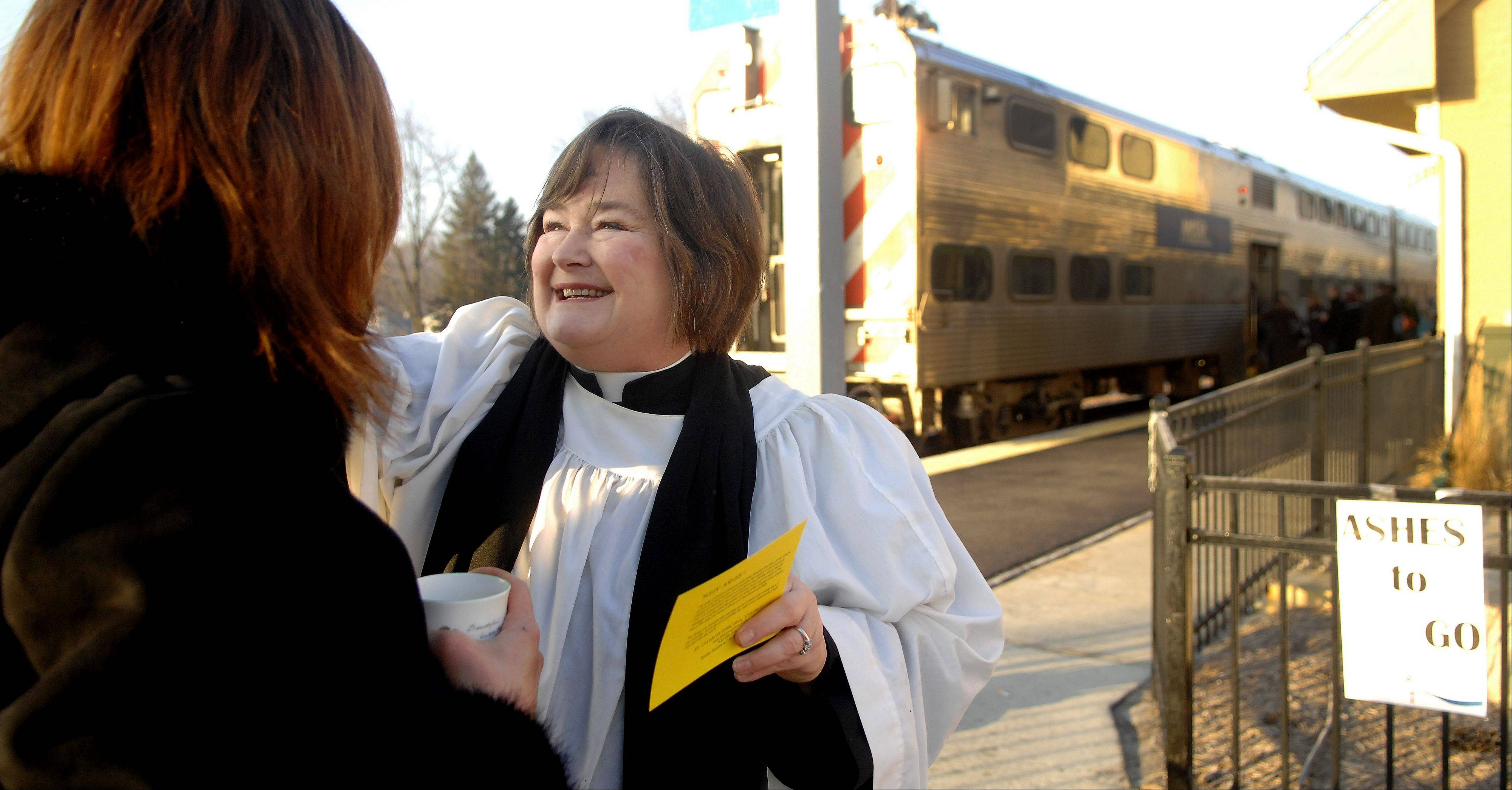 Deacon Liz Meade of St. Charles Episcopal Church administers ashes to a commuter headed to her train at the Geneva Metra station Wednesday morning. The church has been doing Ashes To Go at the site for the past three years.
