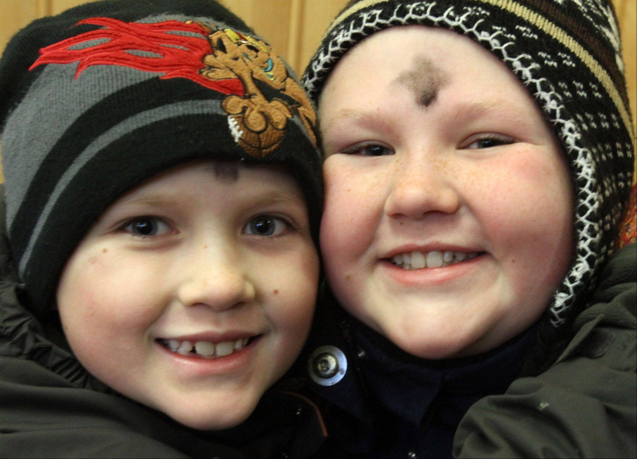 Sean Cunningham, 8, left, and his sister Erin, 11, both of Arlington Heights volunteered to help the Rev. Terry Keehan of Holy Family Catholic Community Church in Inverness give commuters ashes for Ash Wednesday at the Palatine train station.
