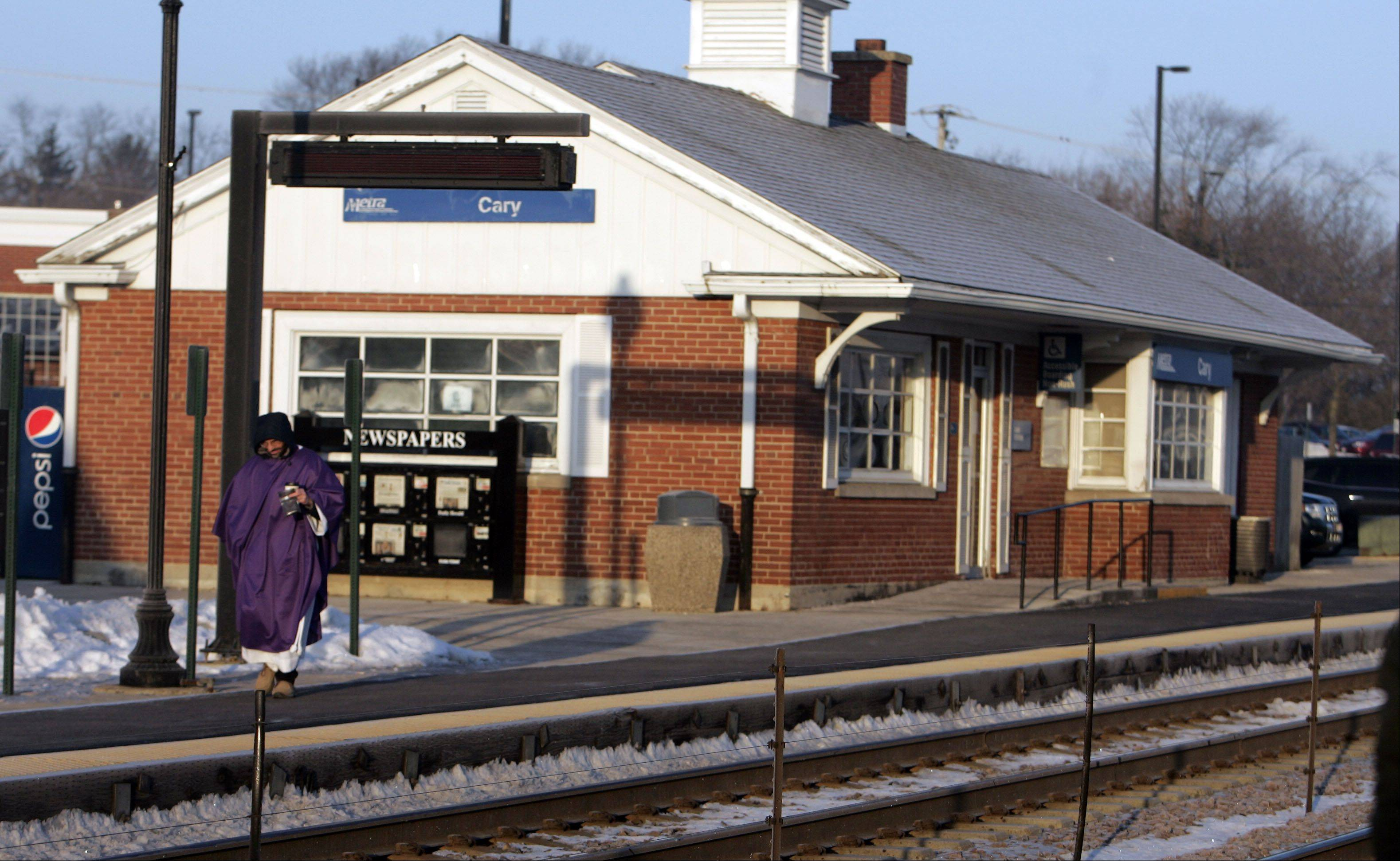 Father Manny Borg of St. Nicholas Episcopal Church in Elk Grove Village makes his way to the train tracks to disperse ashes to commuters at the Cary Metra Station Wednesday February 13, 2013.