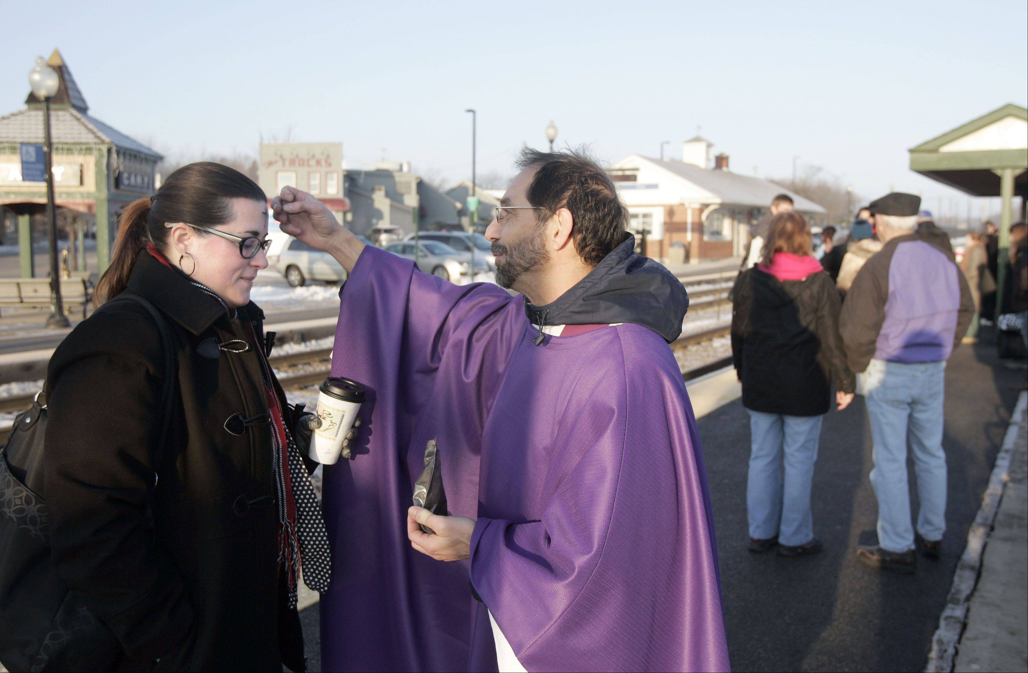 Father Manny Borg of St. Nicholas Episcopal Church in Elk Grove Village disperses ashes to Kelly McGuigan of Lake in the Hills as she starts her commute at the Cary Metra Station Wednesday February 13, 2013.