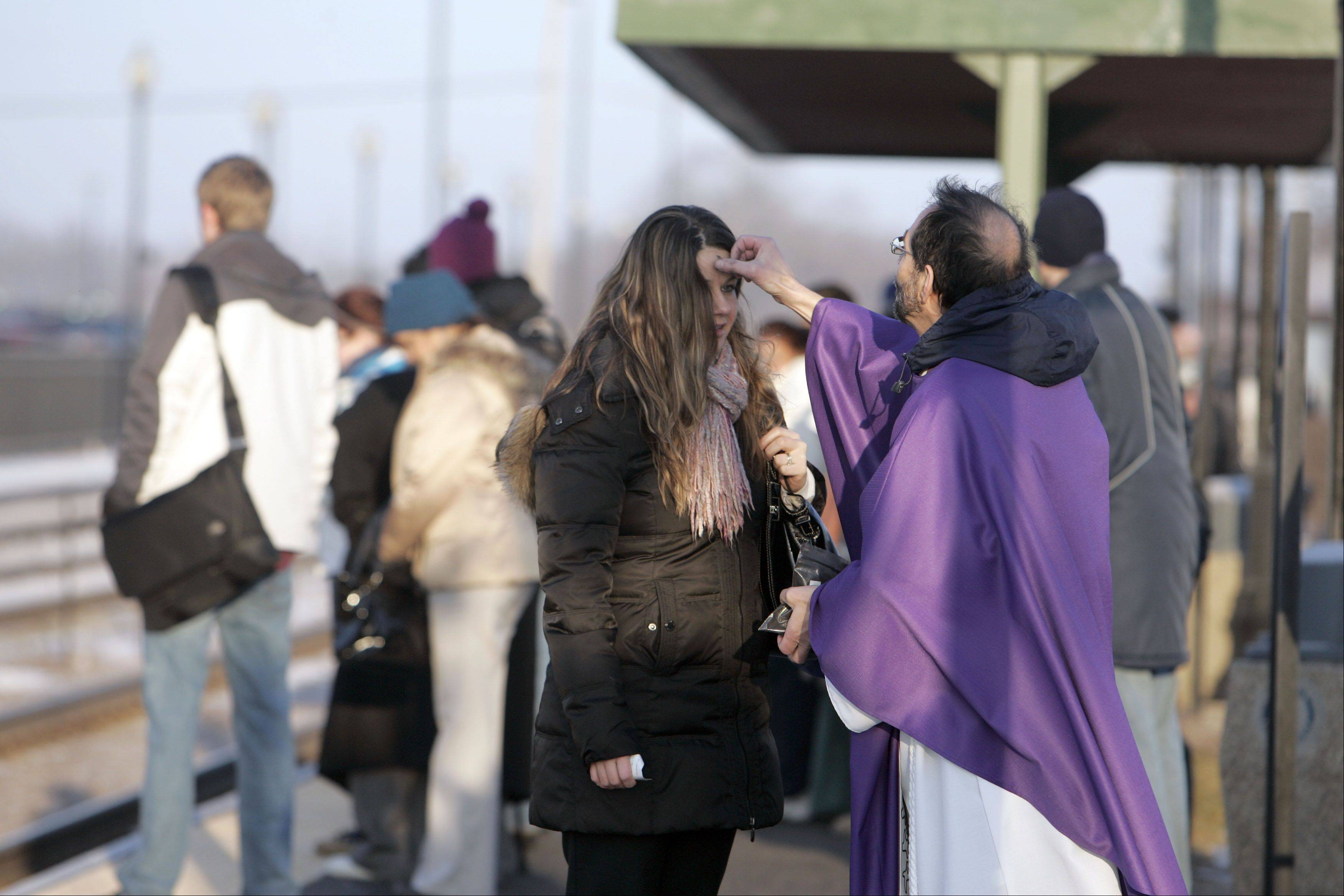 Father Manny Borg of St. Nicholas Episcopal Church in Elk Grove Village disperses ashes to an unidentified commuter at the Cary Metra Station Wednesday February 13, 2013.