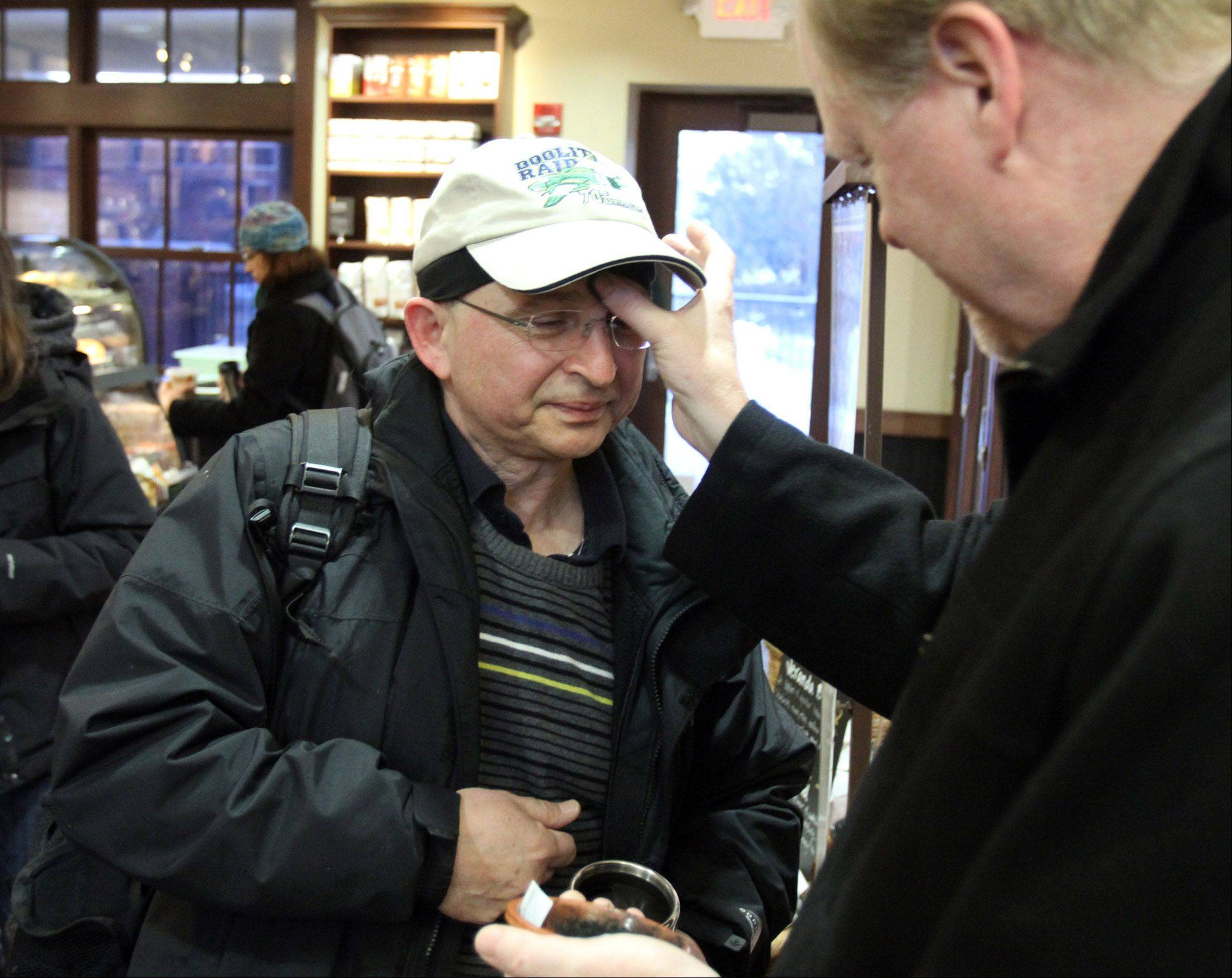 Father Terry Keehan with Holy Family Catholic Community Church in Inverness gives Roman Golash of Palatine ashes for Ash Wednesday inside the Palatine train station.