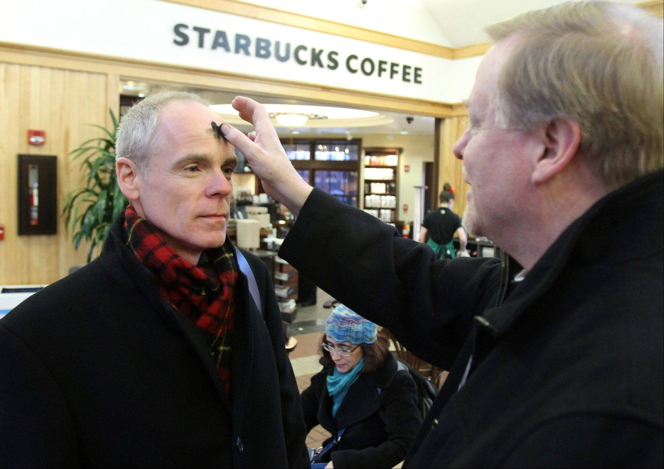 Tim McChesney of Inverness receives ashes from Father Terry Keehan with Holy Family Catholic Community Church in Inverness for Ash Wednesday at the Palatine train station.