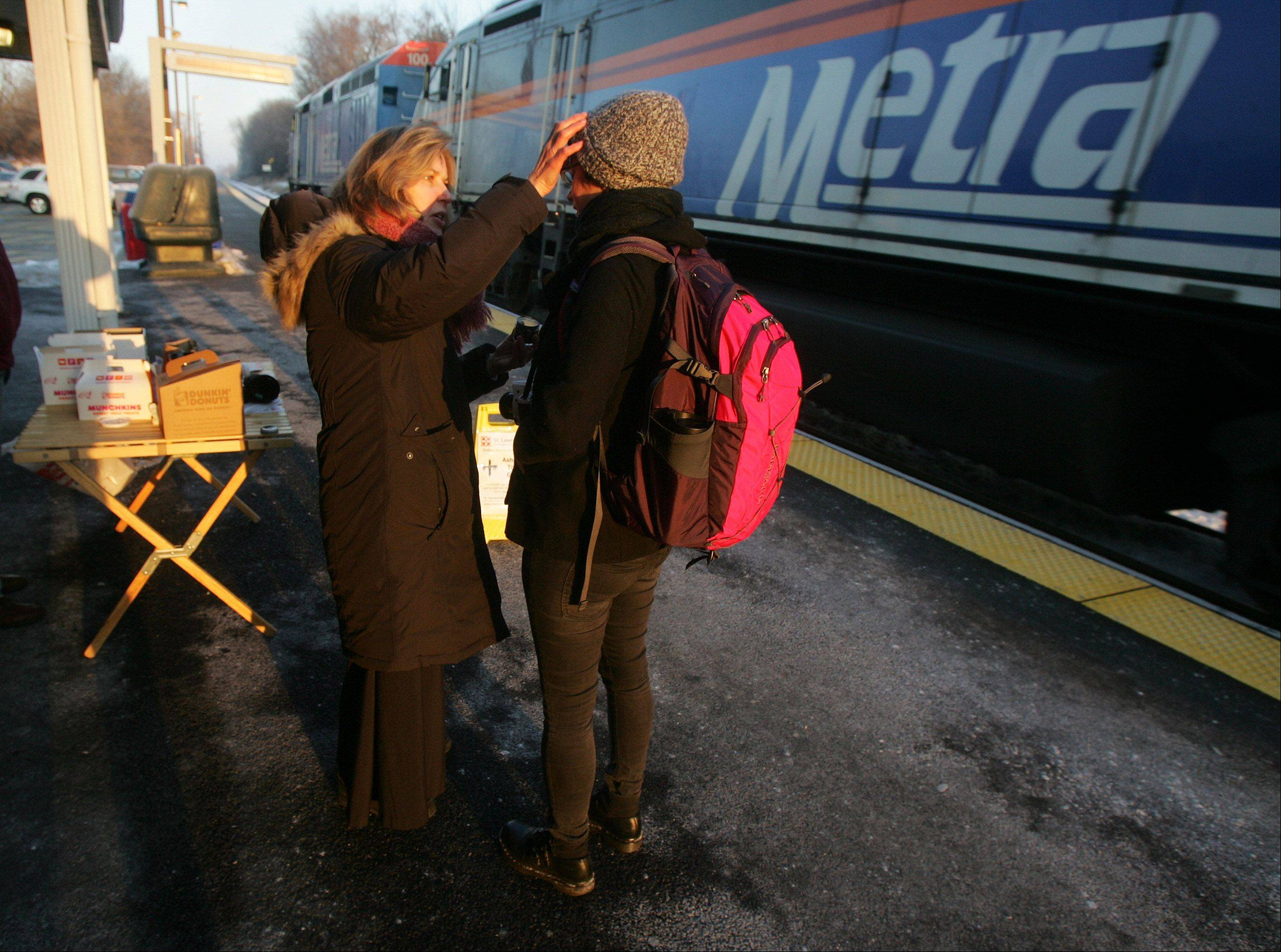 "Rev. Patti Snickenberger, from St. Lawrence Episcopal Church in Libertyville, places ashes on the forehead of Jillian Walther, of Libertyville, on Ash Wednesday at the Libertyville Metra Station as part of the ""Ashe To Go"" program. This is part of a nationwide movement for clergy to visit transit stops, street corners and other public places to help people participate in the religious observance."