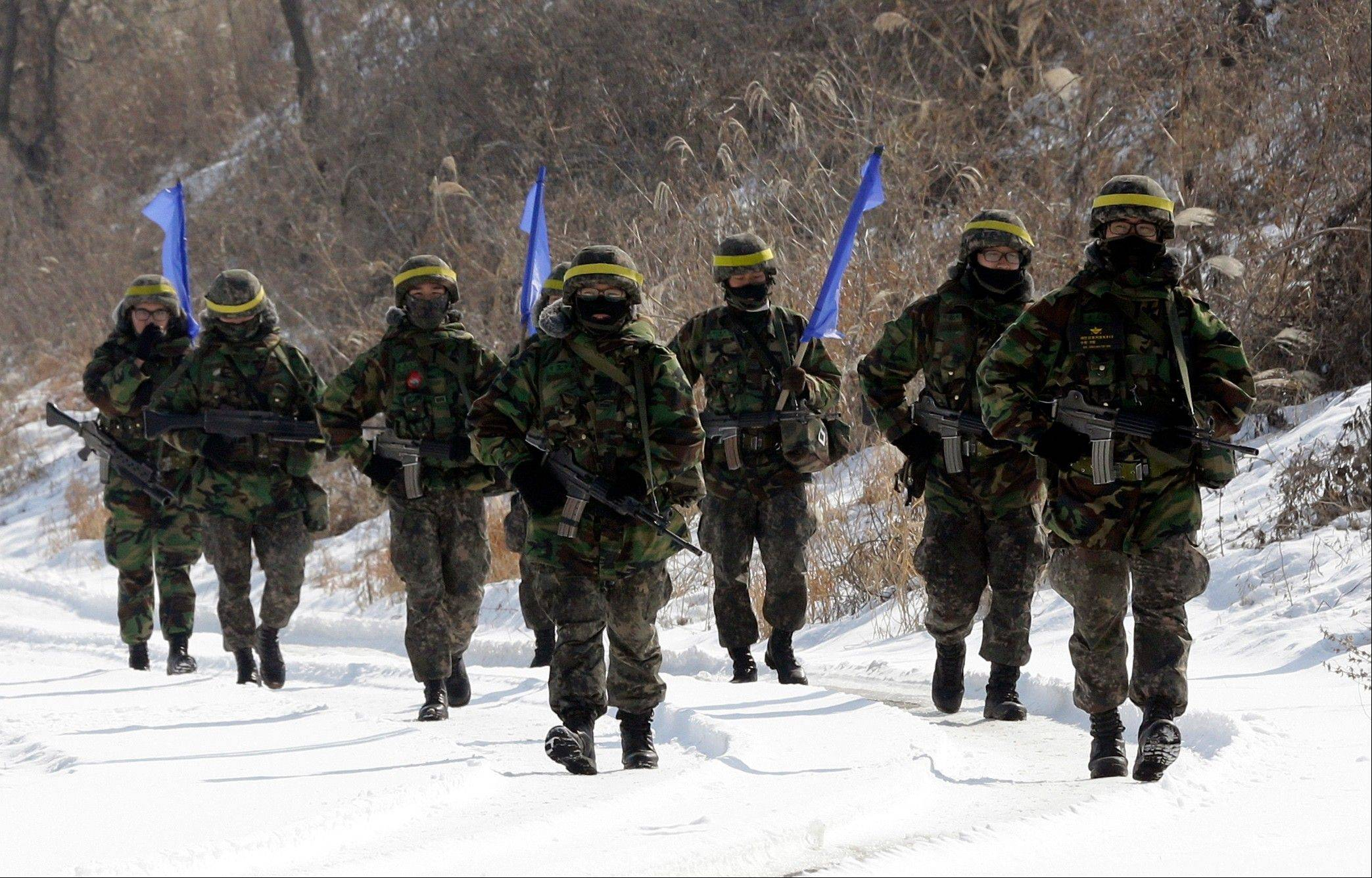 South Korean army soldiers walk on a snow covered road during an exercise near the border village of Panmunjom, which has separated the two Koreas since the Korean War, in Paju, north of Seoul, South Korea, Wednesday, Feb. 13, 2013. A day after North Korea defied U.N. warnings with a nuclear test, Pyongyang's neighbors turned Wednesday to the business of bolstering their military preparations and sending out scientists to determine whether the detonation was as successful as the North claimed.