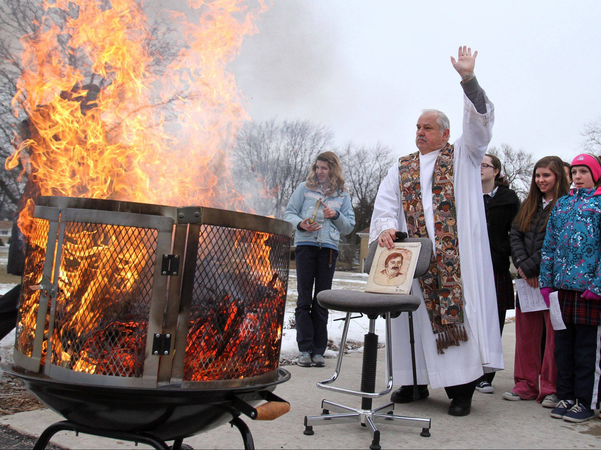 The Rev. Tom Rzepiela oversees palm burning Tuesday afternoon at St. Thomas of Villanova School in Palatine as students look on. The ashes will be used for Ash Wednesday.