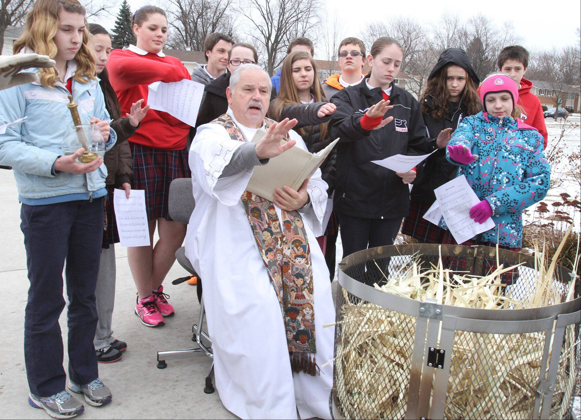 Students at St. Thomas of Villanova School in Palatine look on as the Rev. Tom Rzepiela oversees palm burning Tuesday afternoon. The ashes will be used for Ash Wednesday.