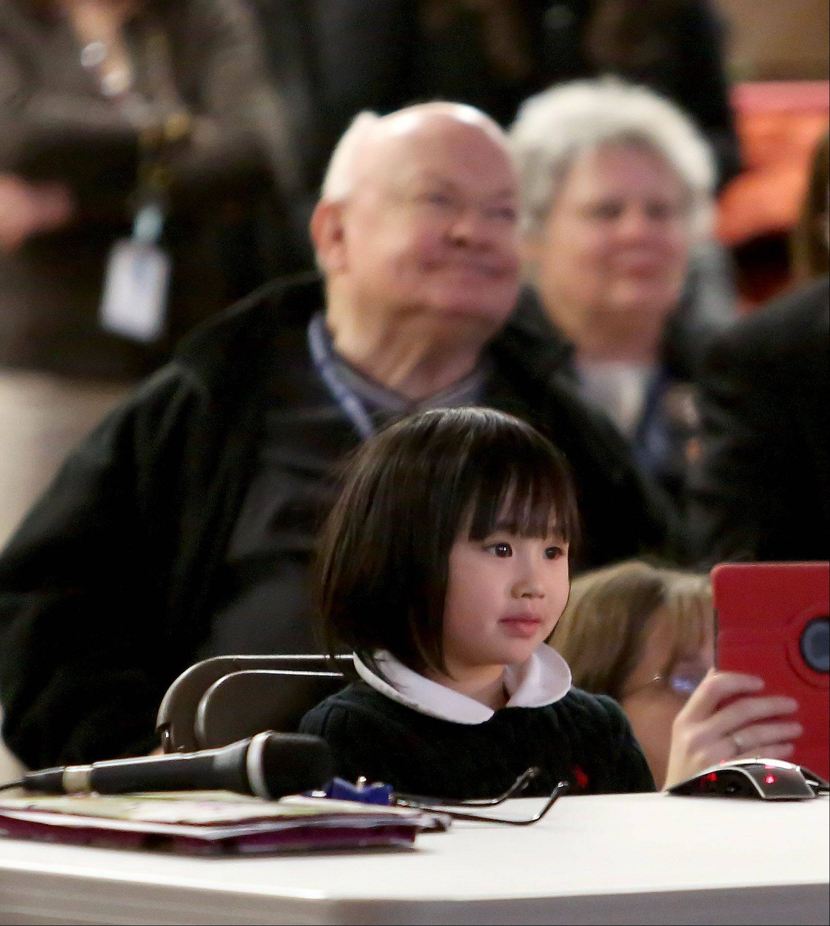 With Mayor George Pradel sitting nearby at St. Raphael School in Naperville, first-grader Miya Lin listens to her question being answered by Cmdr. Kevin Ford from aboard the International Space Station.