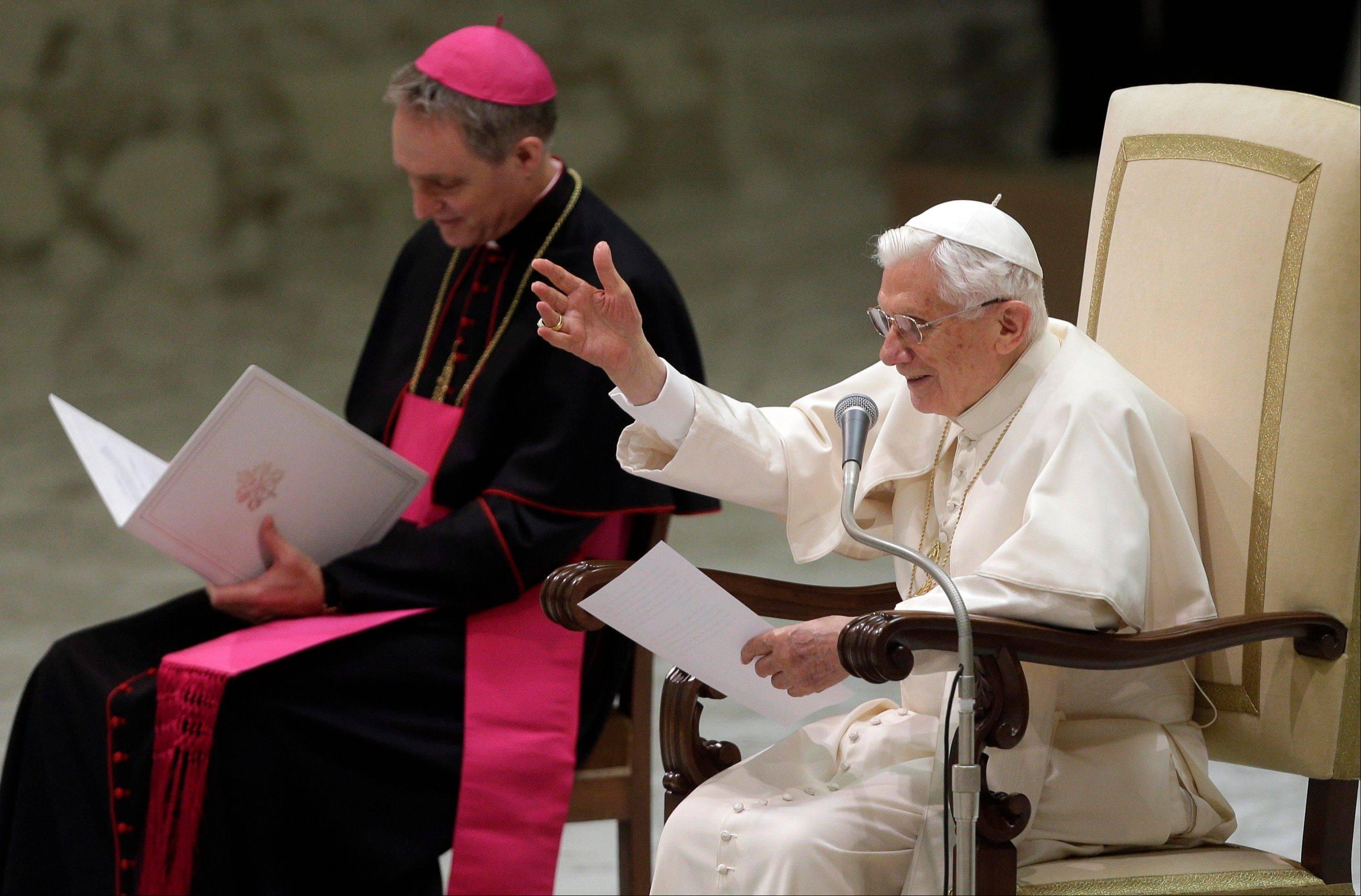 "Pope Benedict XVI is flanked by his private secretary Archbishop Georg Ganswein as he reads a message during his weekly general audience at the Vatican Wednesday. Looking tired but serene, Pope Benedict XVI told thousands of faithful Wednesday he was stepping down for ""the good of the church."""