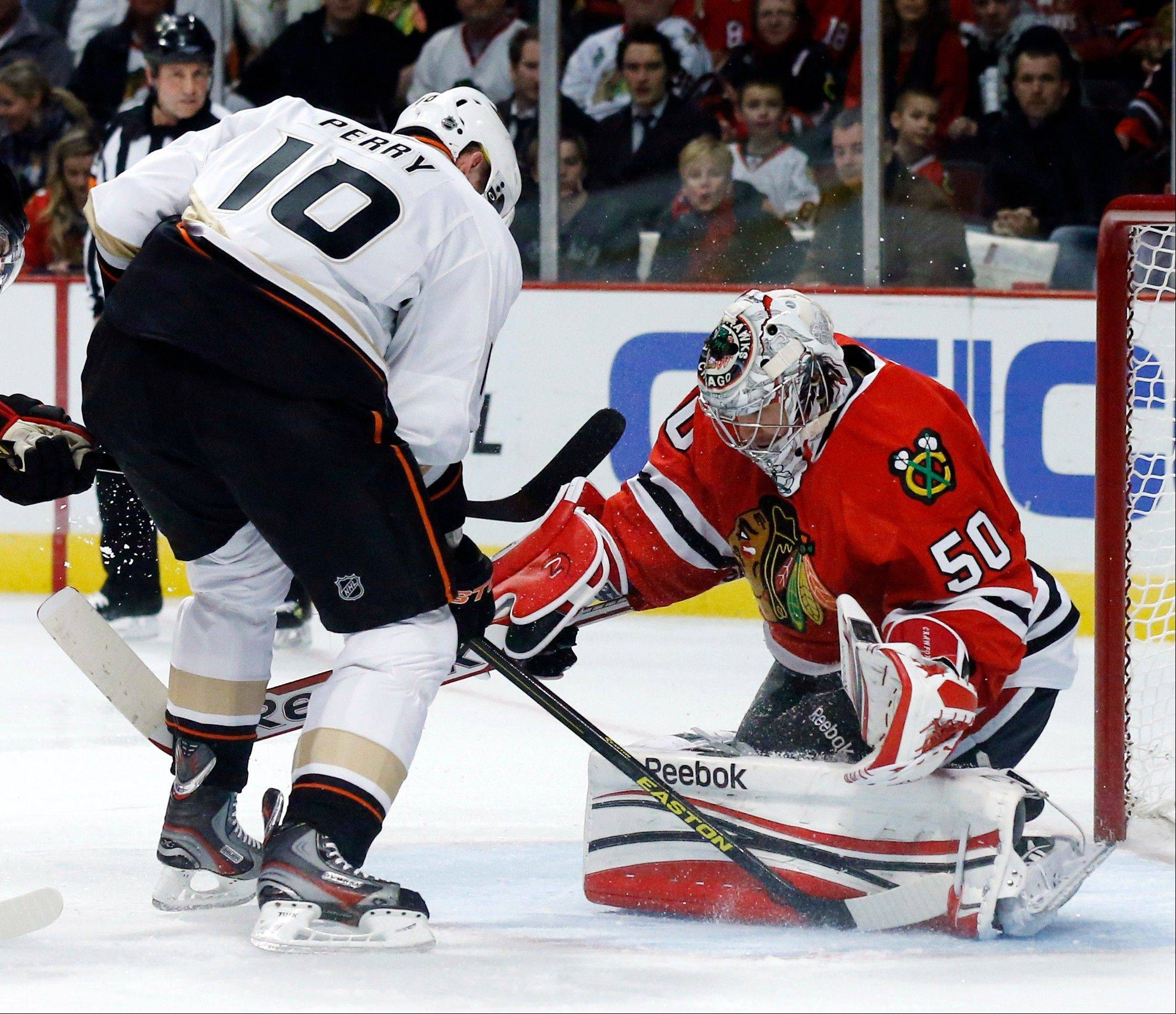 Blackhawks goalie Corey Crawford blocks the rebound shot of Anaheim Ducks right wing Corey Perry during Tuesday's first period at United Center.