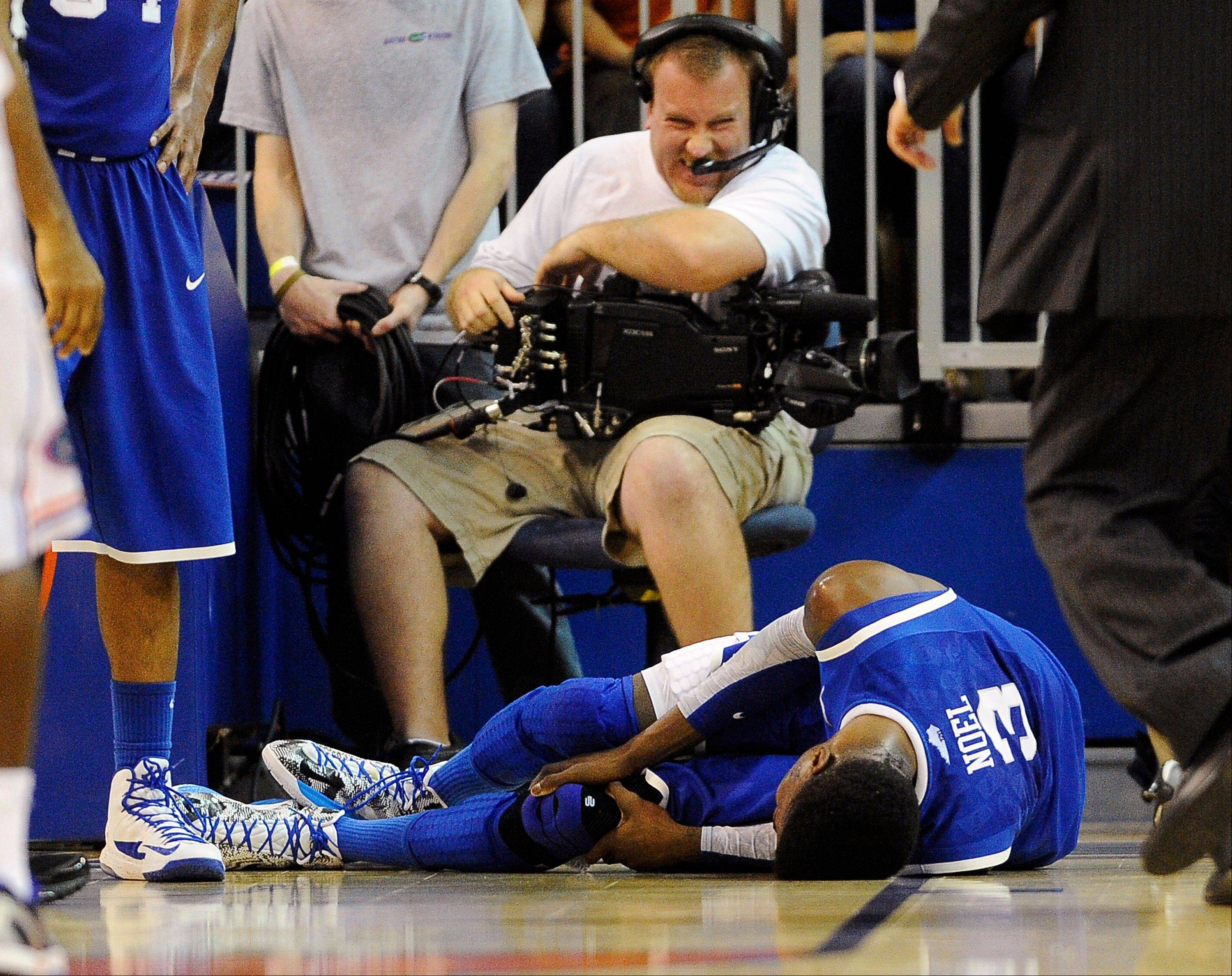 A cameraman grimmaces after a collision with Kentucky forward Nerlens Noel (3) during the second half of an NCAA college basketball game against Florida in Gainesville, Fla., Tuesday, Feb. 12, 2013. Noel injured his left knee and did not return. Florida won 69-52.