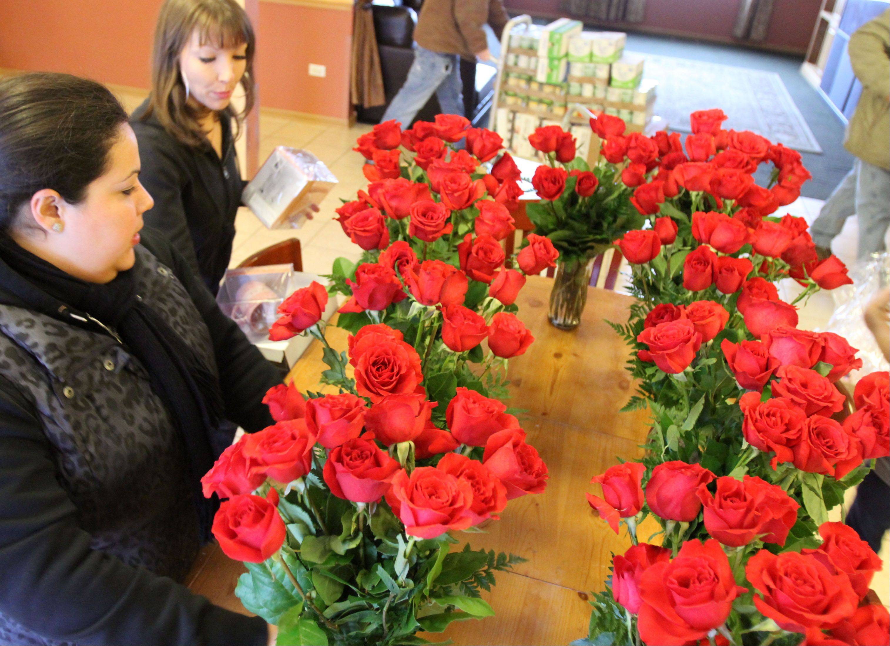 Sarah McClarey, top left, and Cindy Rodriguez deliver 10 dozen roses and gifts to victims of domestic violence and their children at a Northwest suburban safe house Thursday.