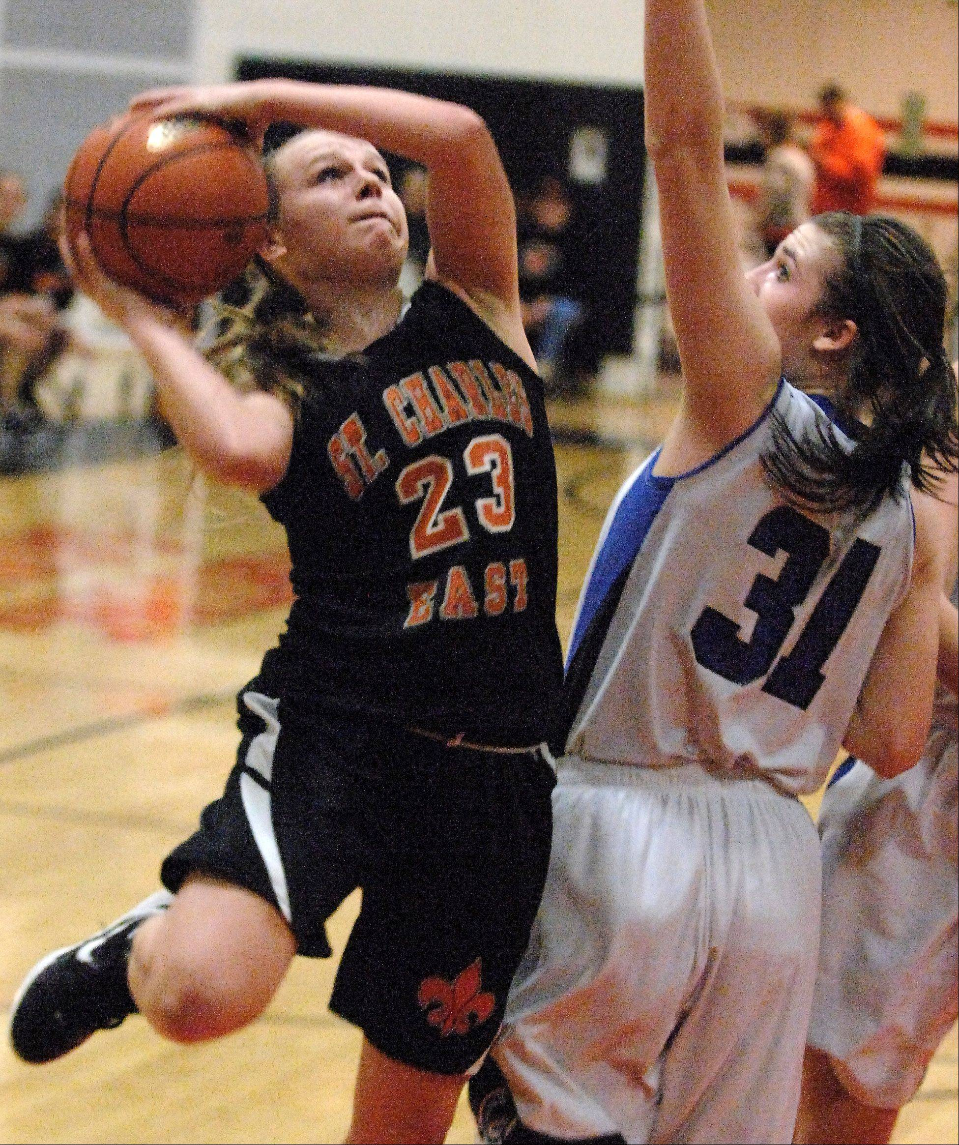 St. Charles East�s Amanda Hilton puts up a shot over Geneva�s Sami Pawlak during Thursday�s regional championship game in St. Charles.