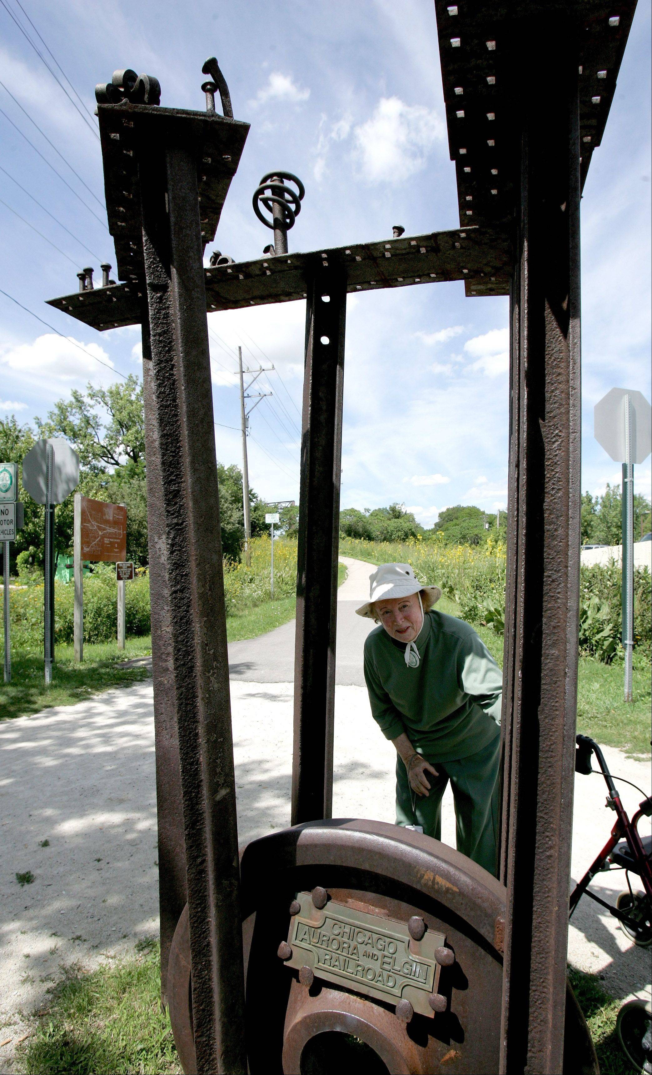 "Jean Mooring looks through a ""Rails to Trails"" sculpture on the Illinois Prairie Path in 2008. She petitioned elected officials in the 1960s to preserve the right of way of the abandoned Chicago, Aurora and Elgin Railroad as open space for the path."