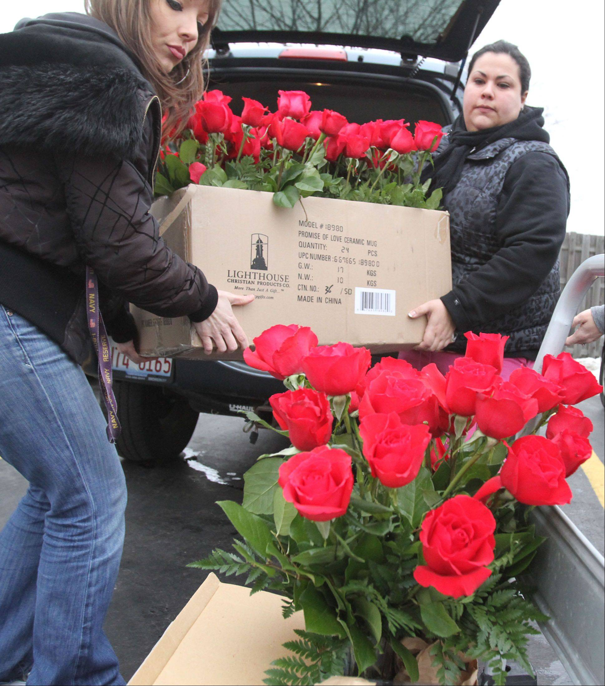 Sarah McClarey, left, and Cindy Rodriguez deliver dozens of roses to a suburban safe house Thursday.