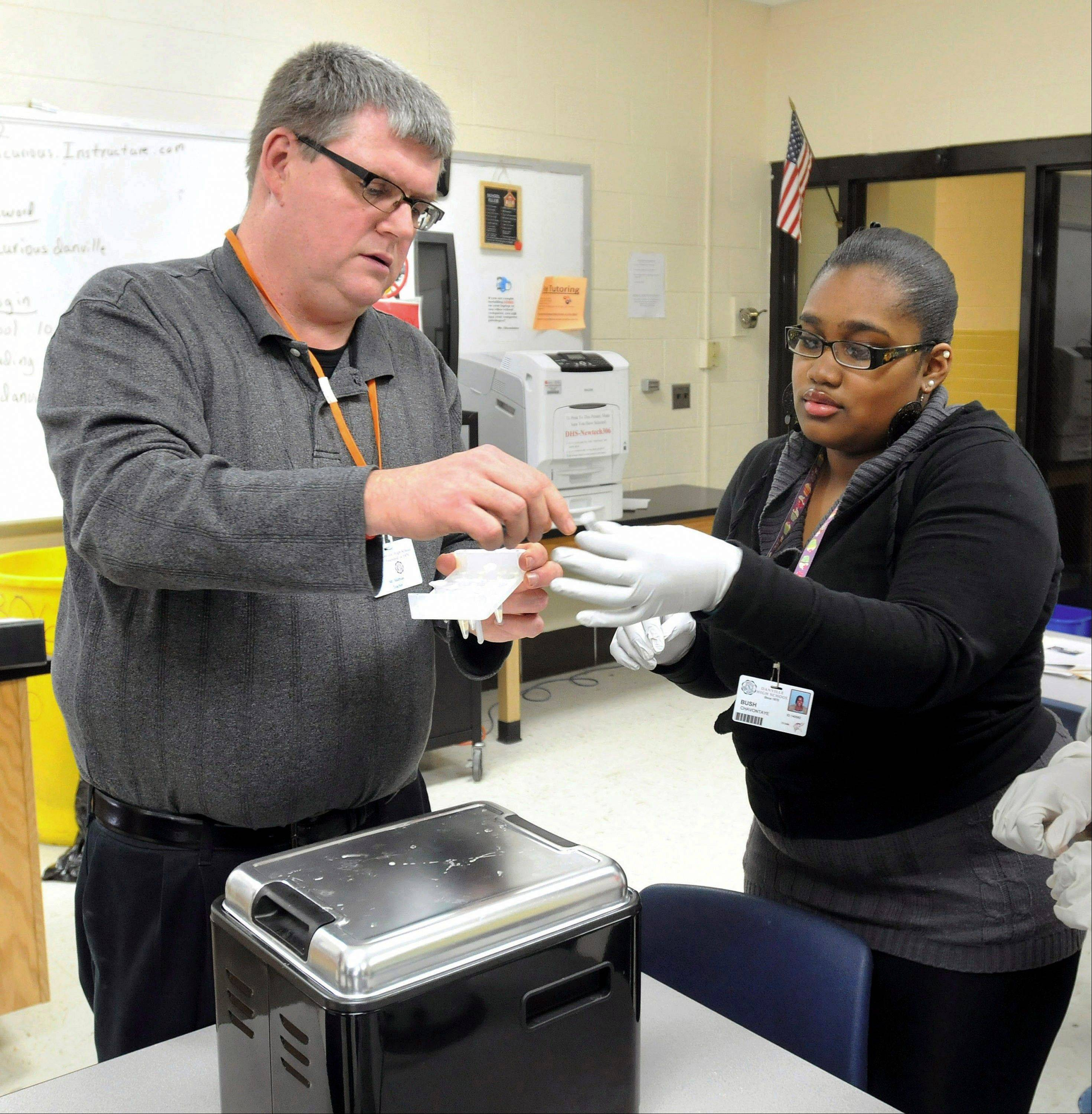 Science teacher Doug Mathias gives a vial with a DNA sample to Chavontaye Bush at Danville High School in Danville.
