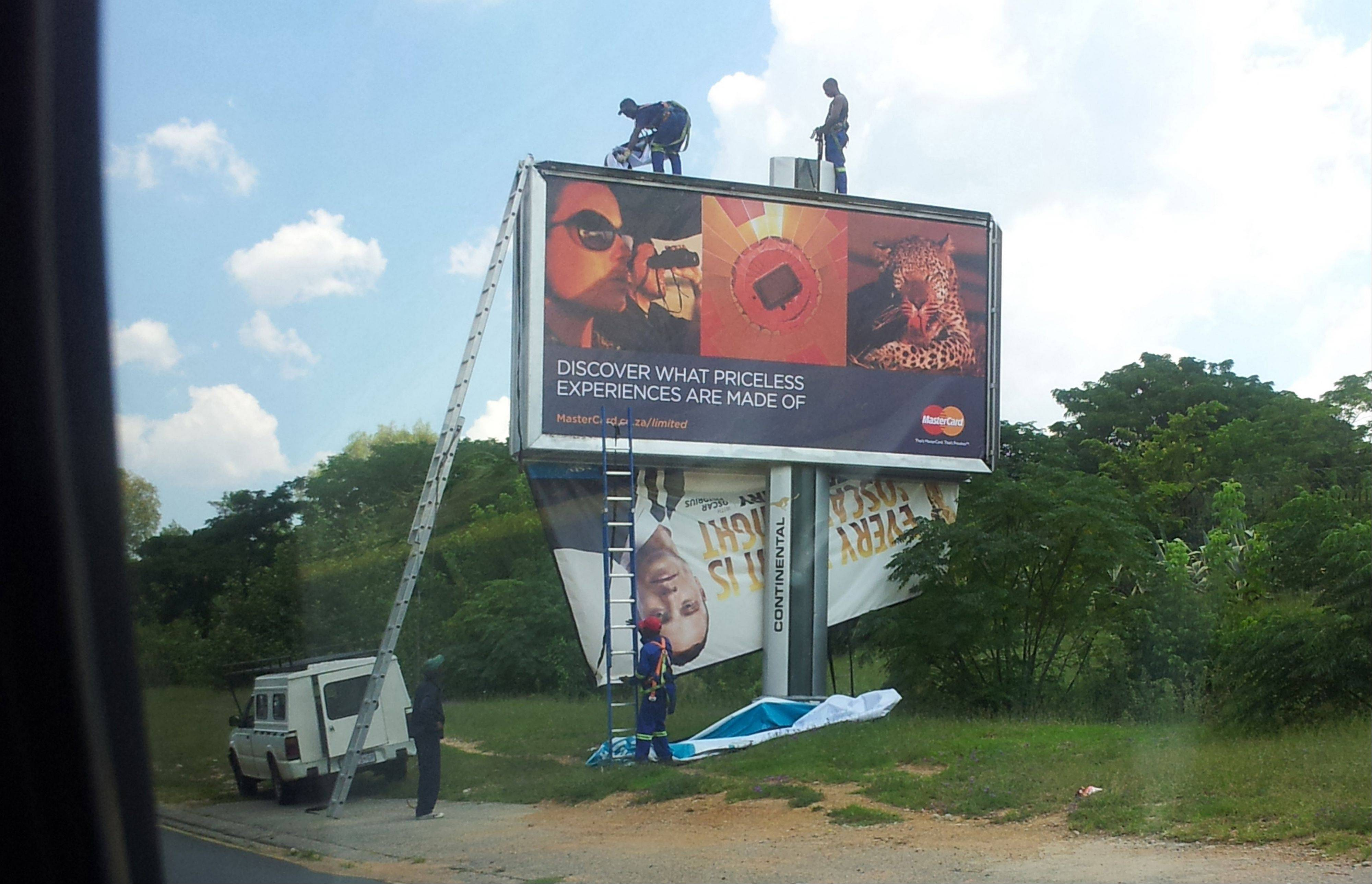 Workers take down a billboard of Olympic athlete Oscar Pistorius endorsing a product in Johannesburg, Thursday, Feb. 14, 2013. Pistorius was charged Thursday with the murder of his girlfriend who was shot inside his home in South Africa.