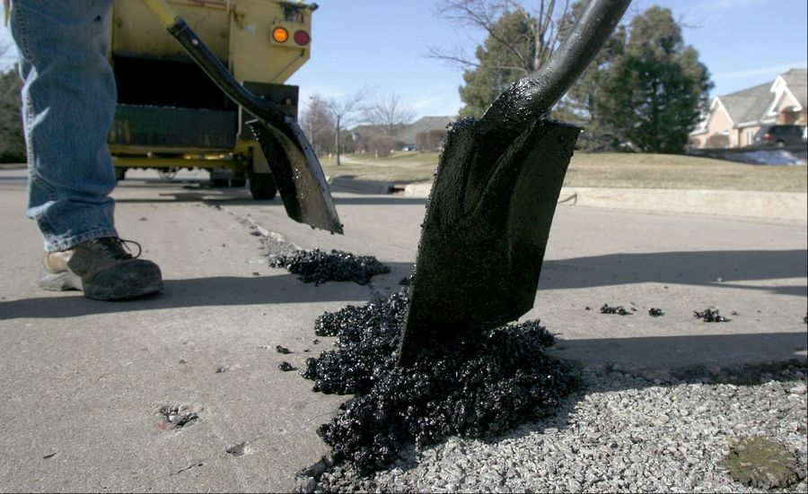 Libertyville public works employees repair potholes along Florsheim Drive in Libertyville last year. The village is about to embark on an unparalleled season of road repairs.