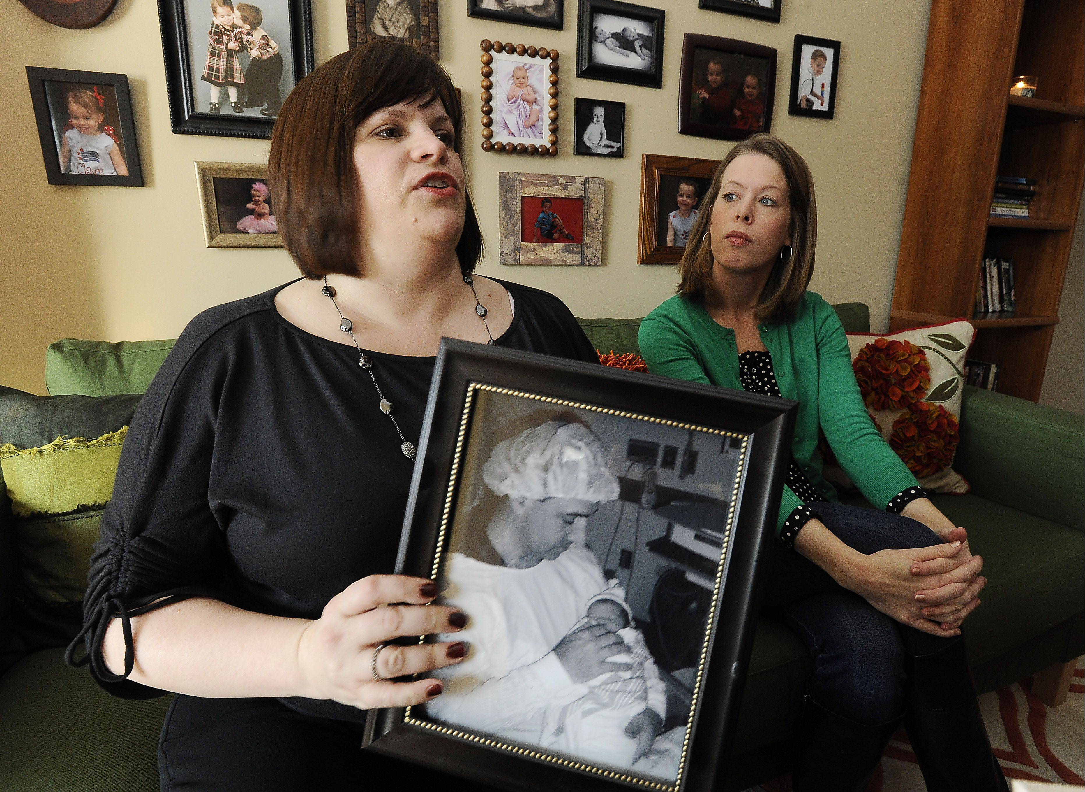 Holding a photograph of her husband cradling their newborn daughter just days before he died, Wendy Diez and friend Laura Dennis, right, explain why they needed to start the Chicagoland Young Widowed Connection. The group hosts a Valentine & Wine event Saturday in Glenview.