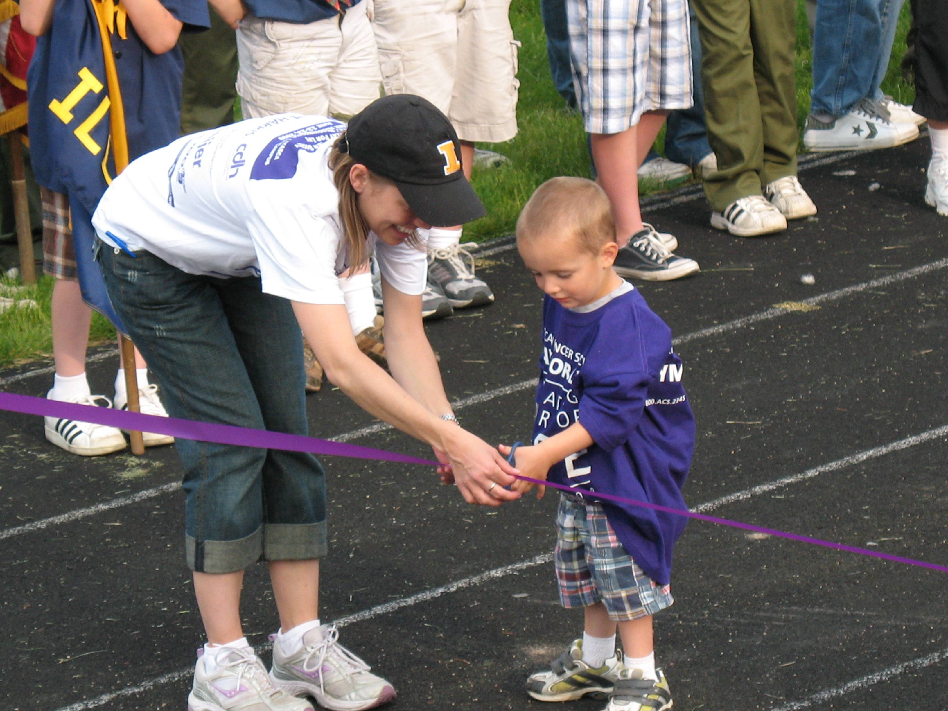 Cancer Survivior Joey Gilliam cuts the ribbon at the Relay For Life Roselle, Bloomingdale, Medinah and Itasca opening ceremony.
