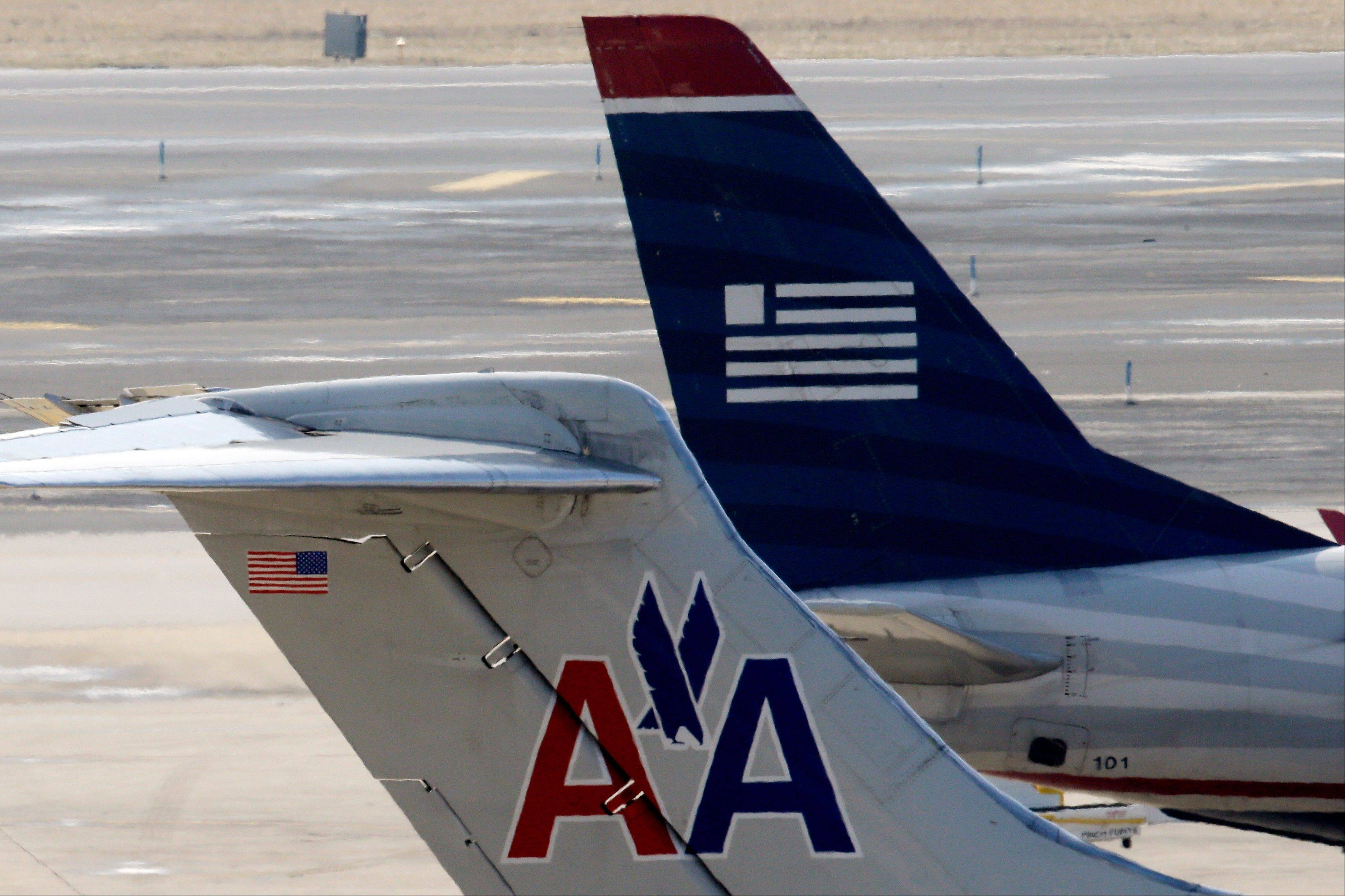 American Airlines and US Airways jets prepare for flight Thursday at a gate at the Philadelphia International Airport.