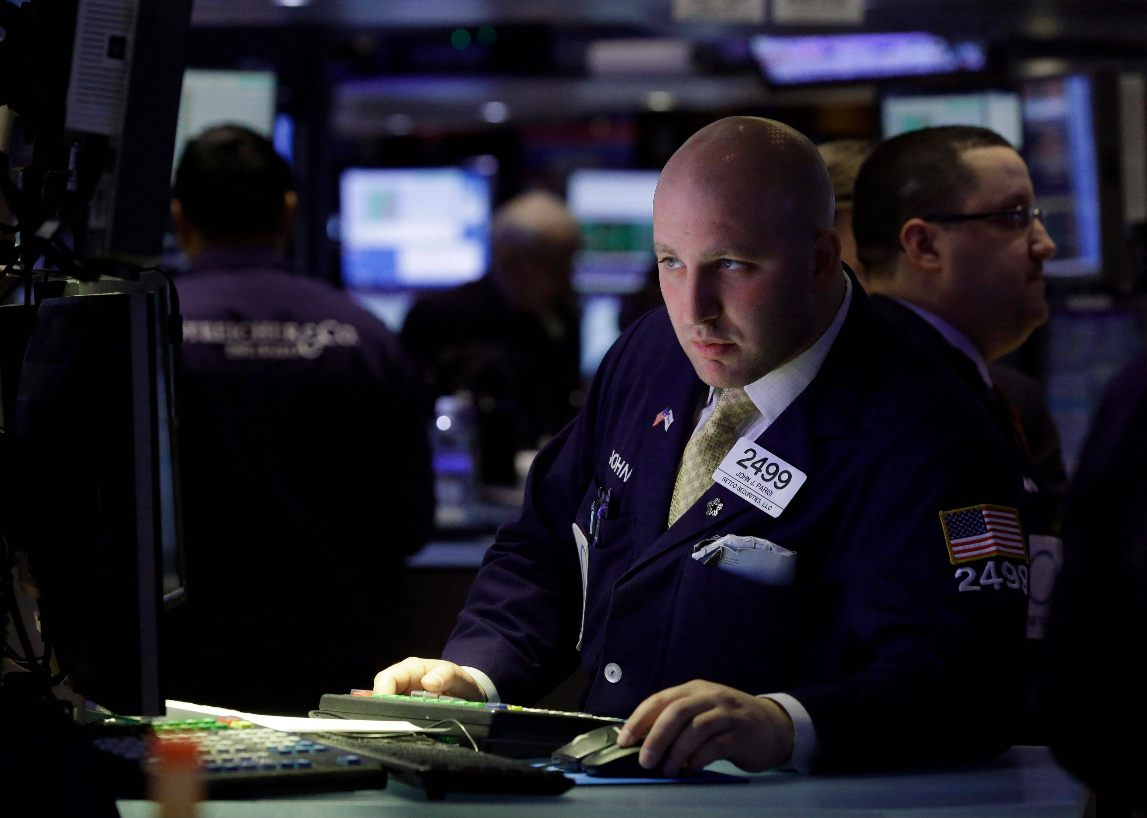 Specialist Joe Parisi works Thursday at his post on the floor of the New York Stock Exchange, in New York. Disappointing news about Germany�s economy sent Asian stock markets down on Friday.
