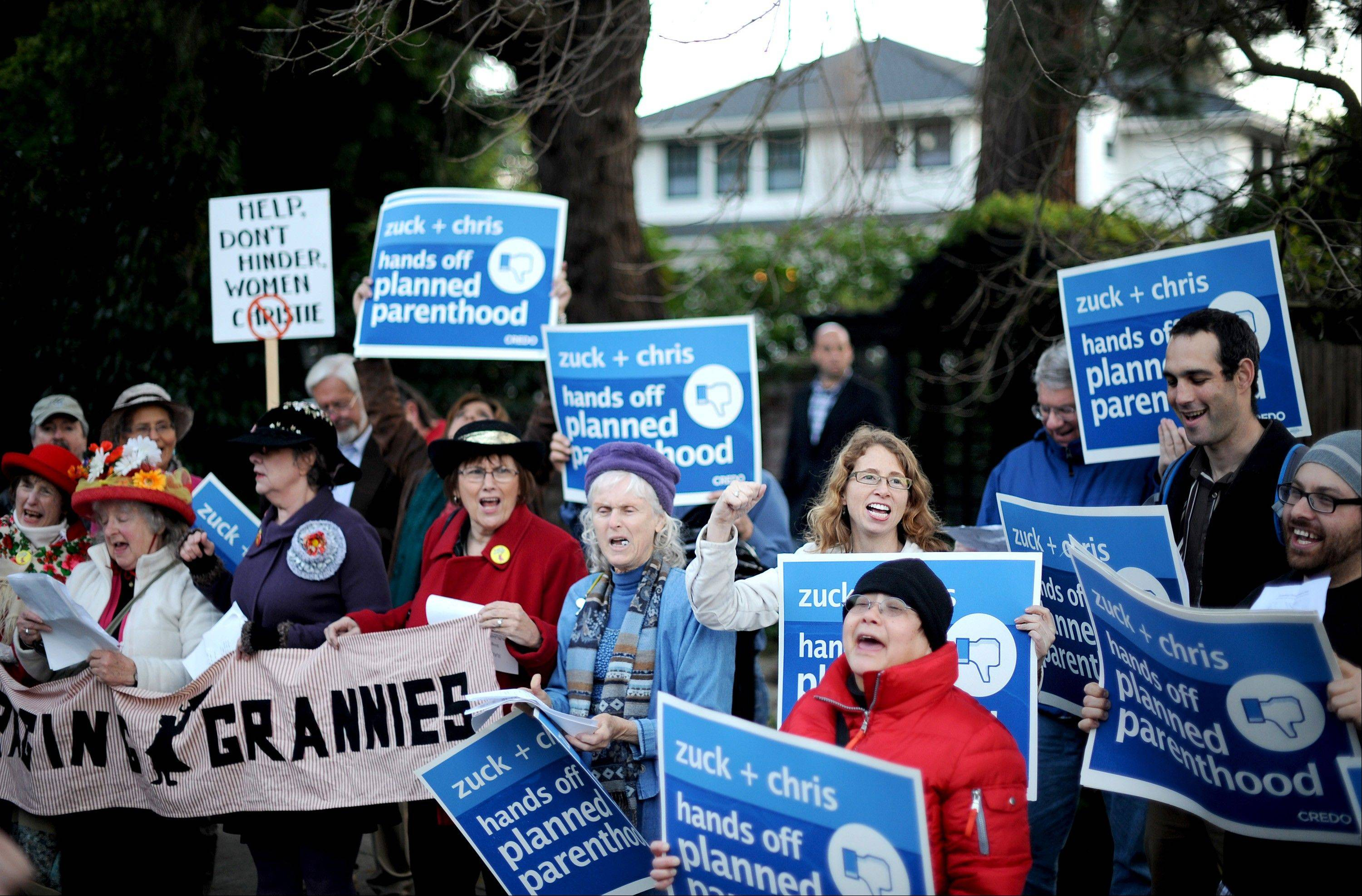 Protesters chant Wednesday outside the home of Mark Zuckerberg, chief executive officer and founder of Facebook Inc., seen in background, in Palo Alto, California. Facebook says it was the target of hackers but no user information was compromised during the attack.