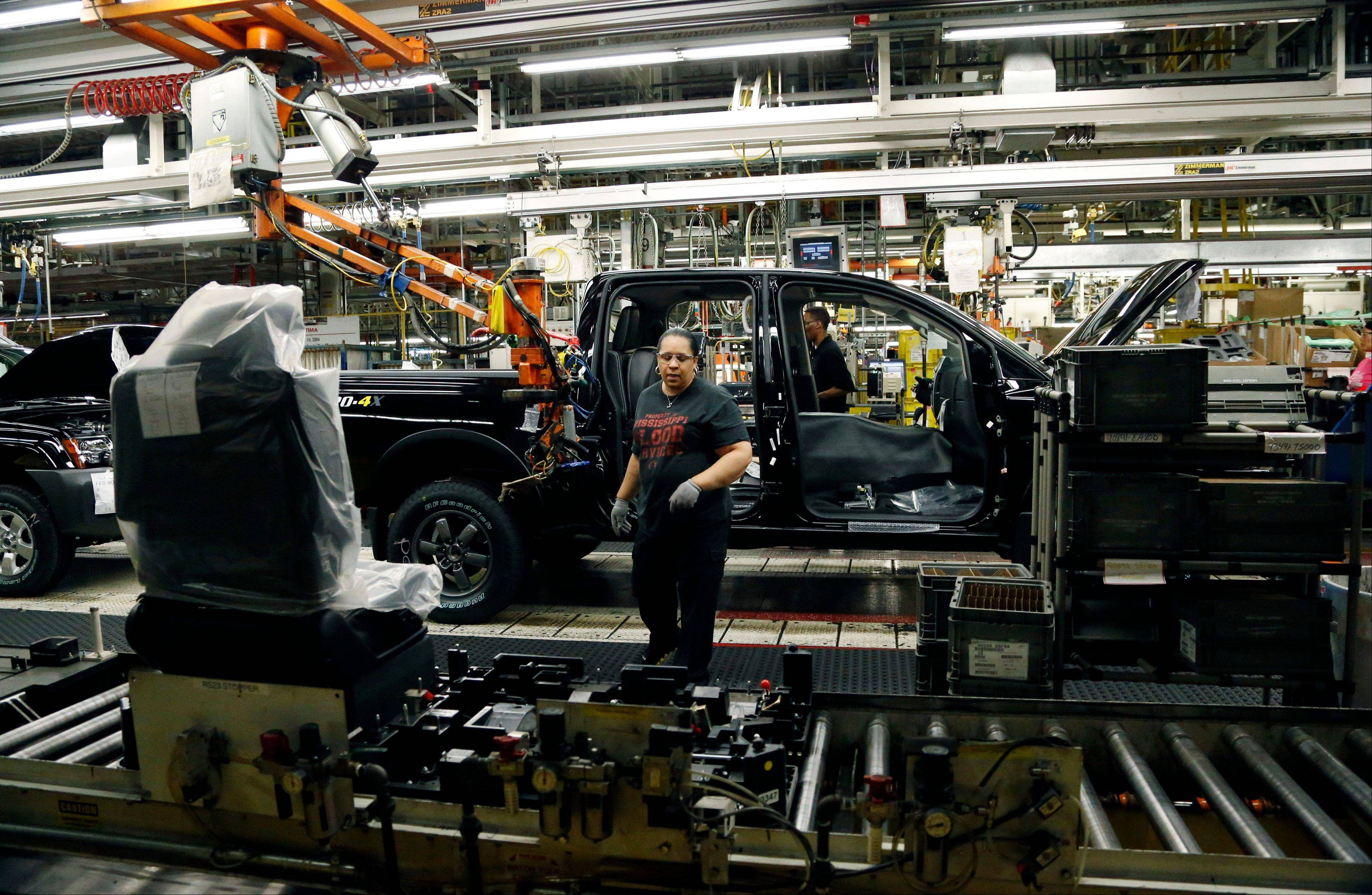 ANissan employee reaches for a seat module to insert into a Titan truck at its Canton, Miss., manufacturing plant.
