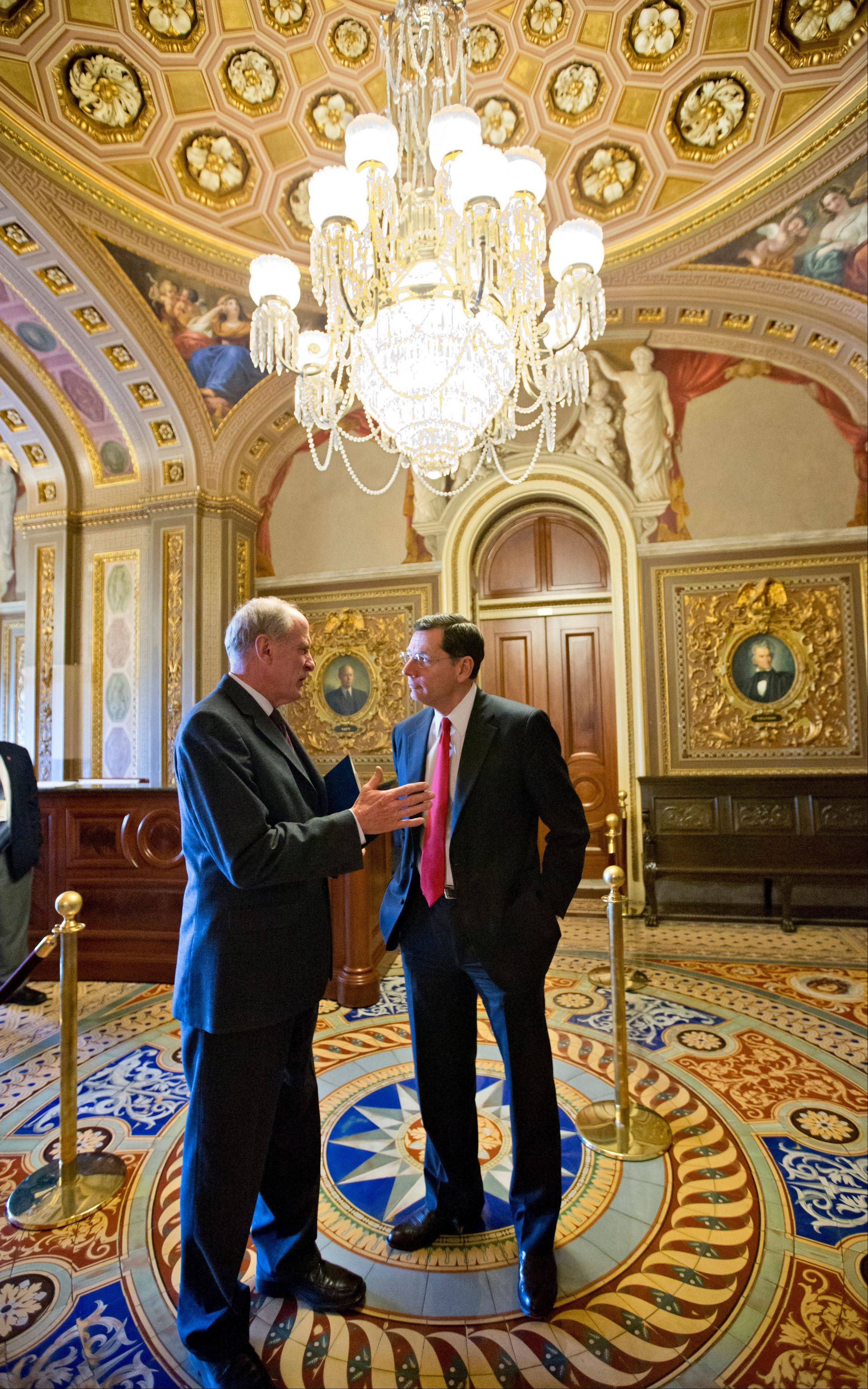 Sen. Dan Coats, an Indiana Repblican, left, and GOP Sen. John Barrasso of Wyoming confer as they leave a GOP caucus Thursday at the Capitol in Washington.