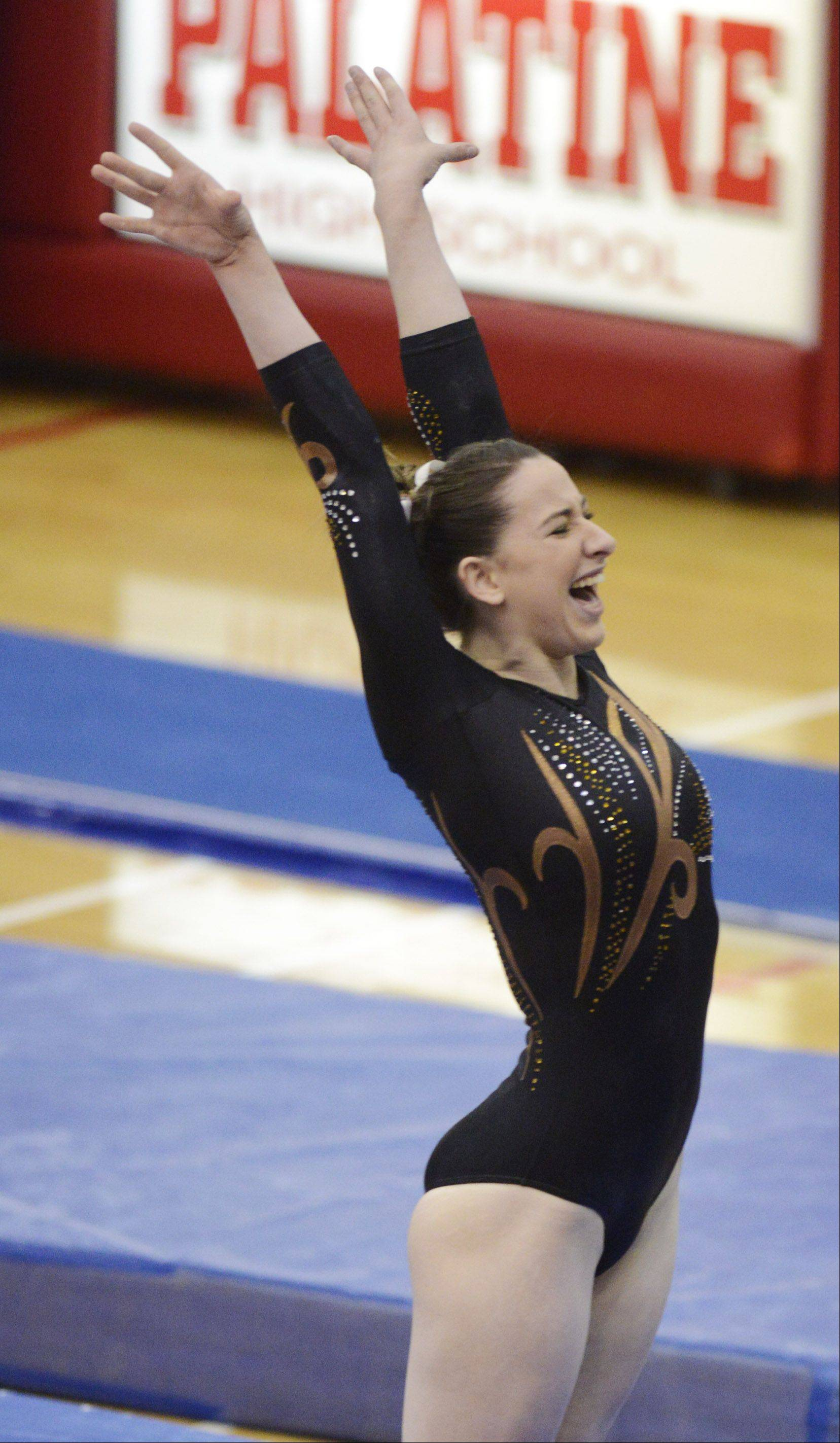 Carmel�s Lauren Feely celebrates her performance on balance beam during the girls gymnastics state meet prelims at Palatine on Friday. The Corsairs senior won the all-around and had the top efforts on floor exercise, vault and beam.