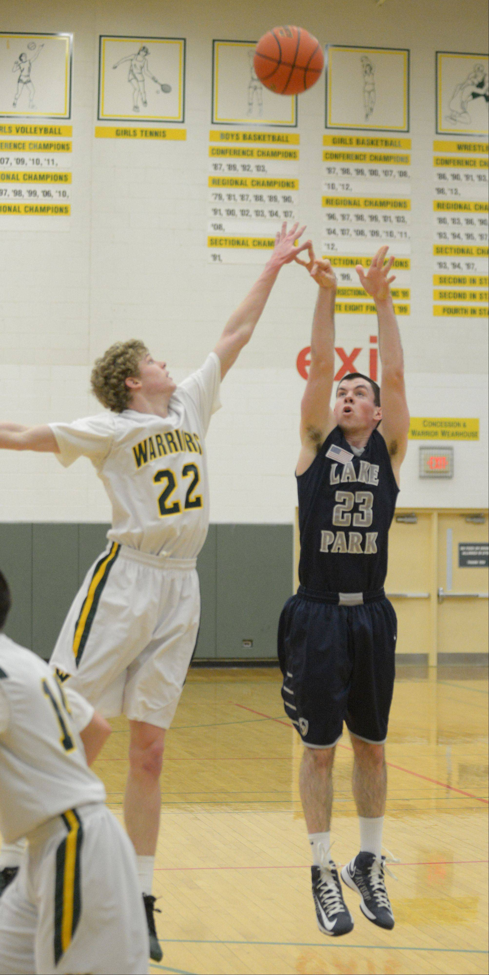 Jack Cordes of Waubonsie,left, attempts to block a shot by Sean Moore of Lake Park during the Lake Park at Waubonsie Valley boys basketball game Friday.