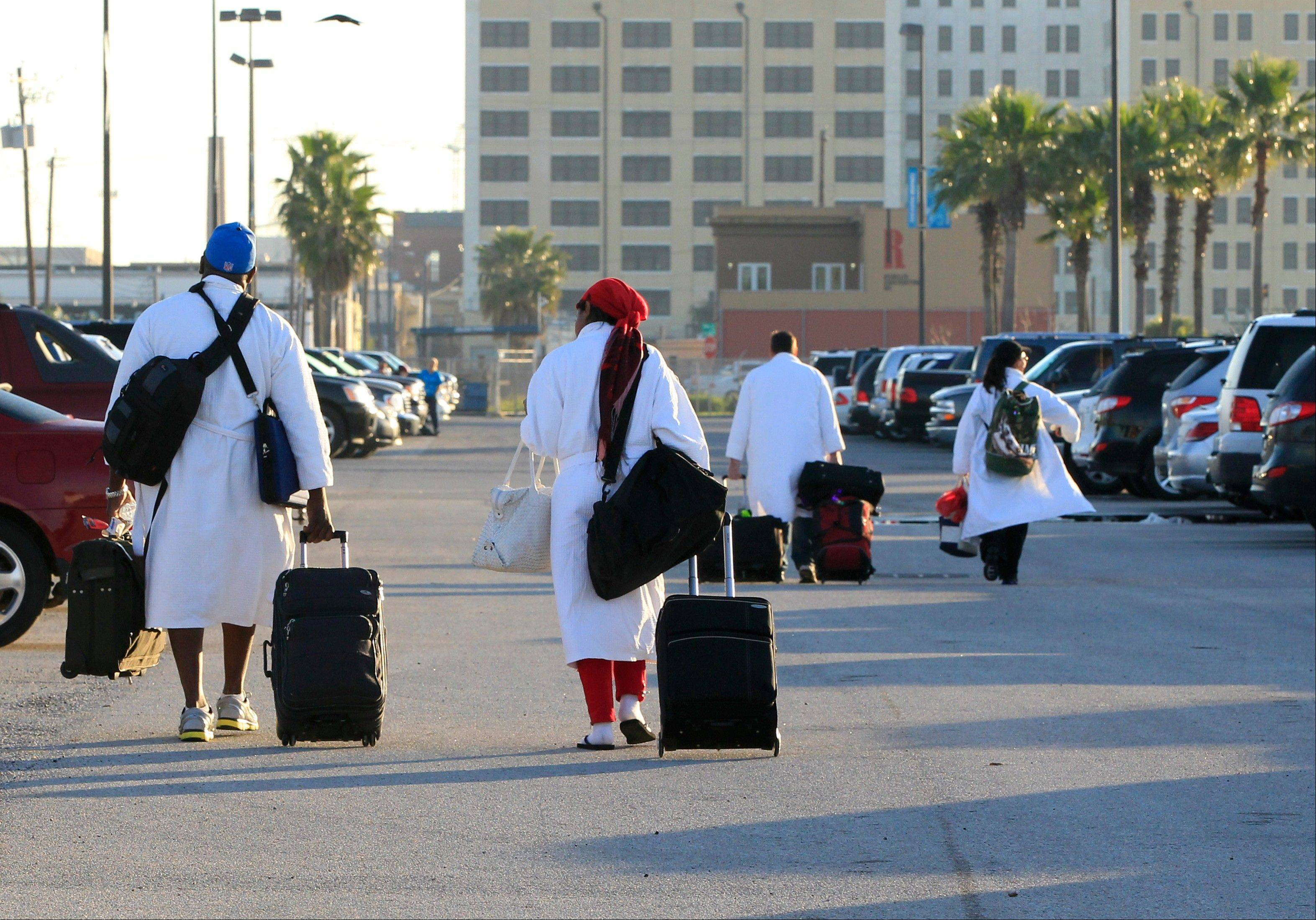 Passengers from the Carnival ship Triumph, all wearing their Carnival bathrobes, head to their cars Friday after arriving in Galveston, Texas from Mobile, Ala.
