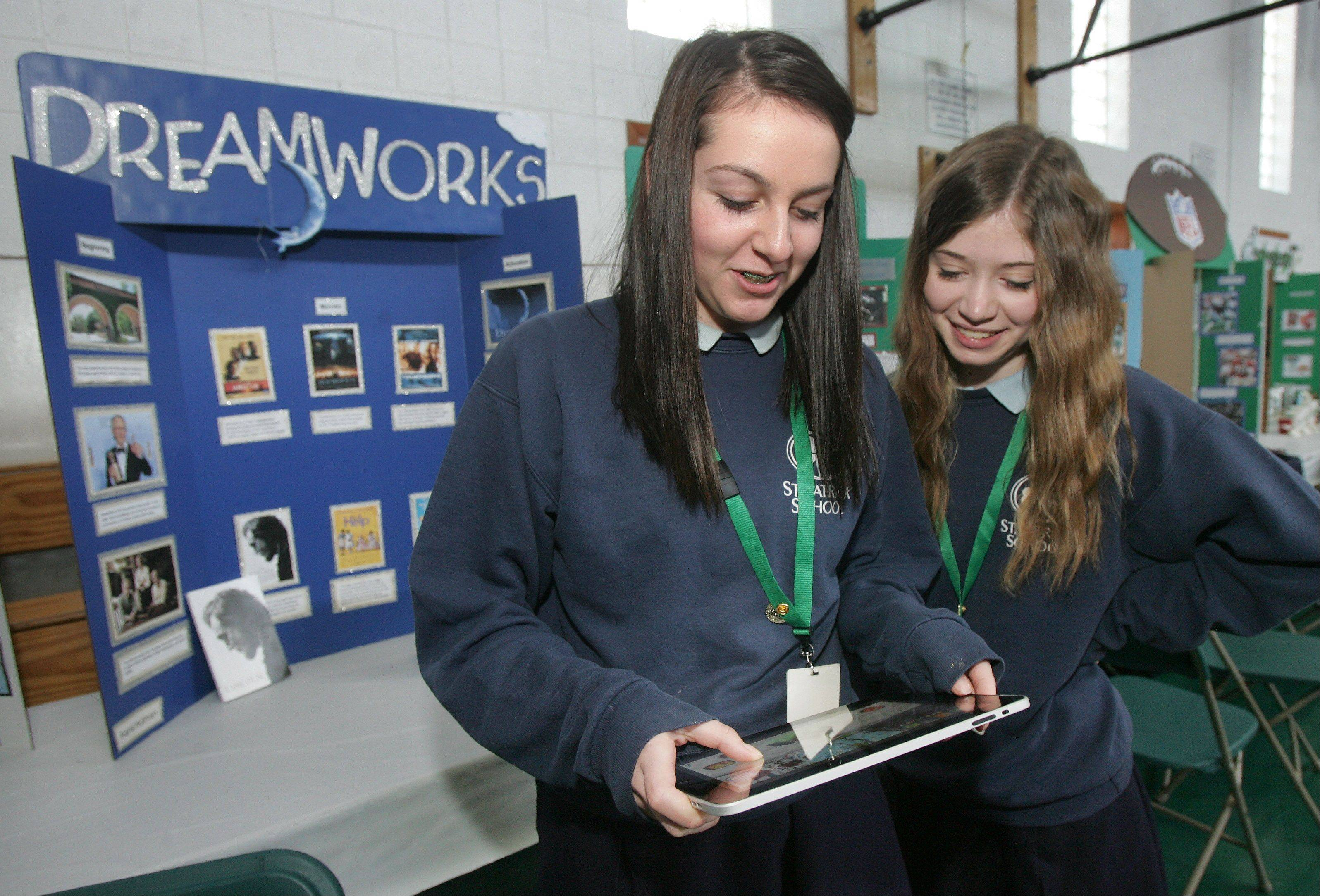 "Eighth-graders Julia Ward, left, and Hana Holman use an iPad to play a DreamWorks game called ""Shrek Kart"" during the Academic Fair at St. Patrick Catholic School in Wadsworth."