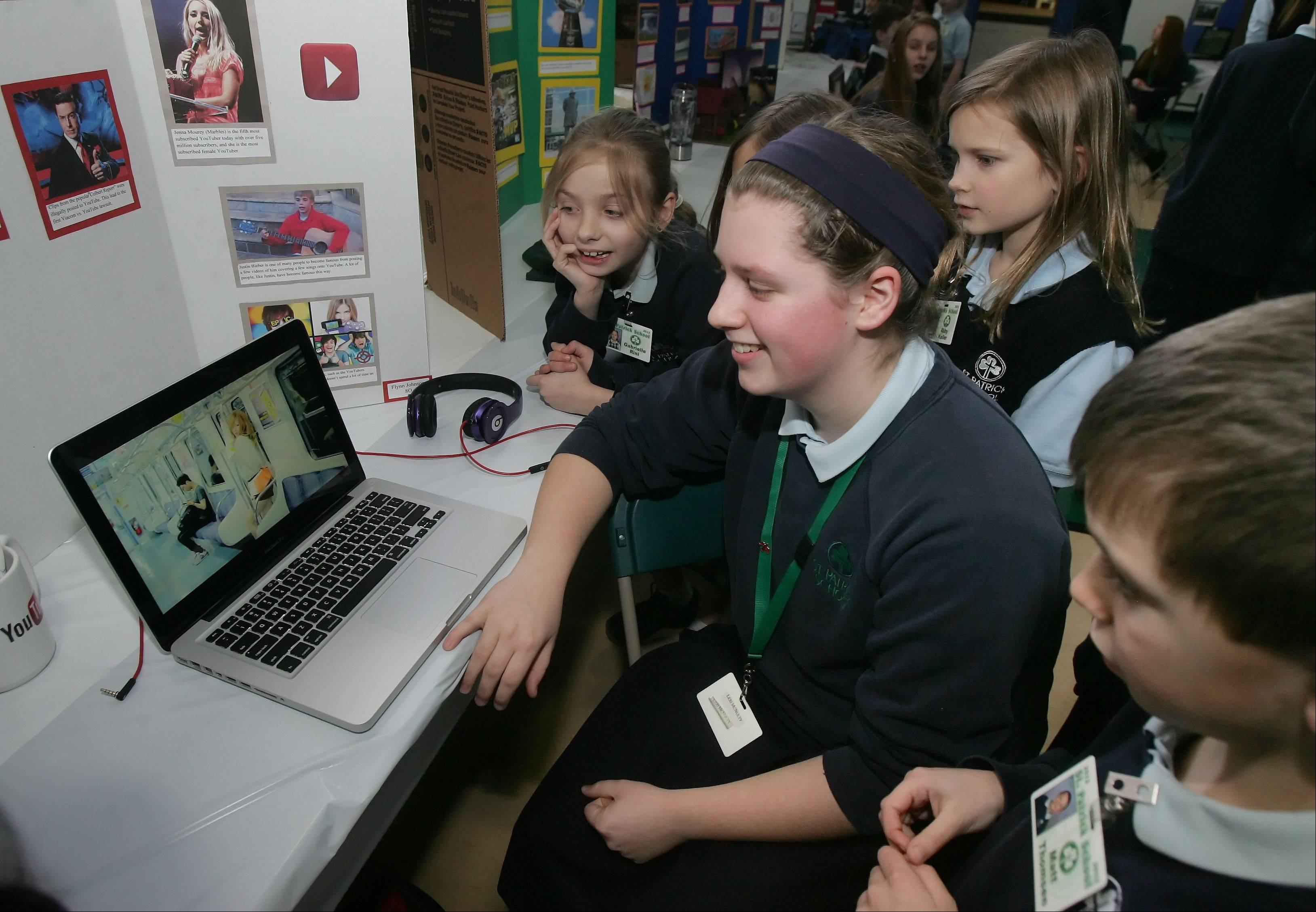 Eighth-grader Flynn Johnson shows videos to third-graders at her YouTube exhibit during the Academic Fair at St. Patrick Catholic School in Wadsworth.