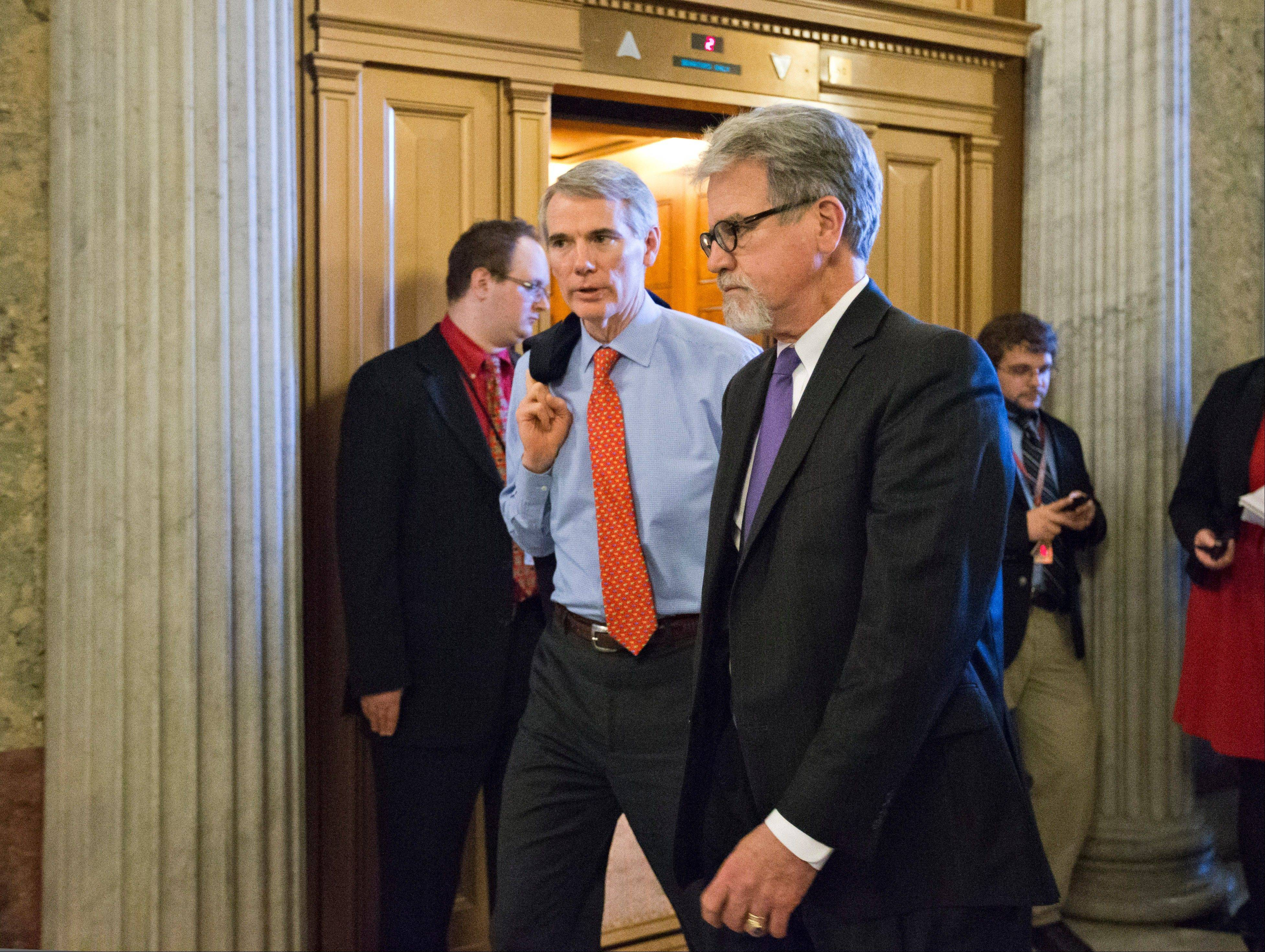 Sen. Tom Coburn, R-Okla., right, and Sen. Rob Portman, R-Ohio, left, arrive for the vote to end debate on the nomination of former GOP senator Chuck Hagel as the nation's next secretary of defense, at the Capitol in Washington, Thursday, Feb. 14, 2013.